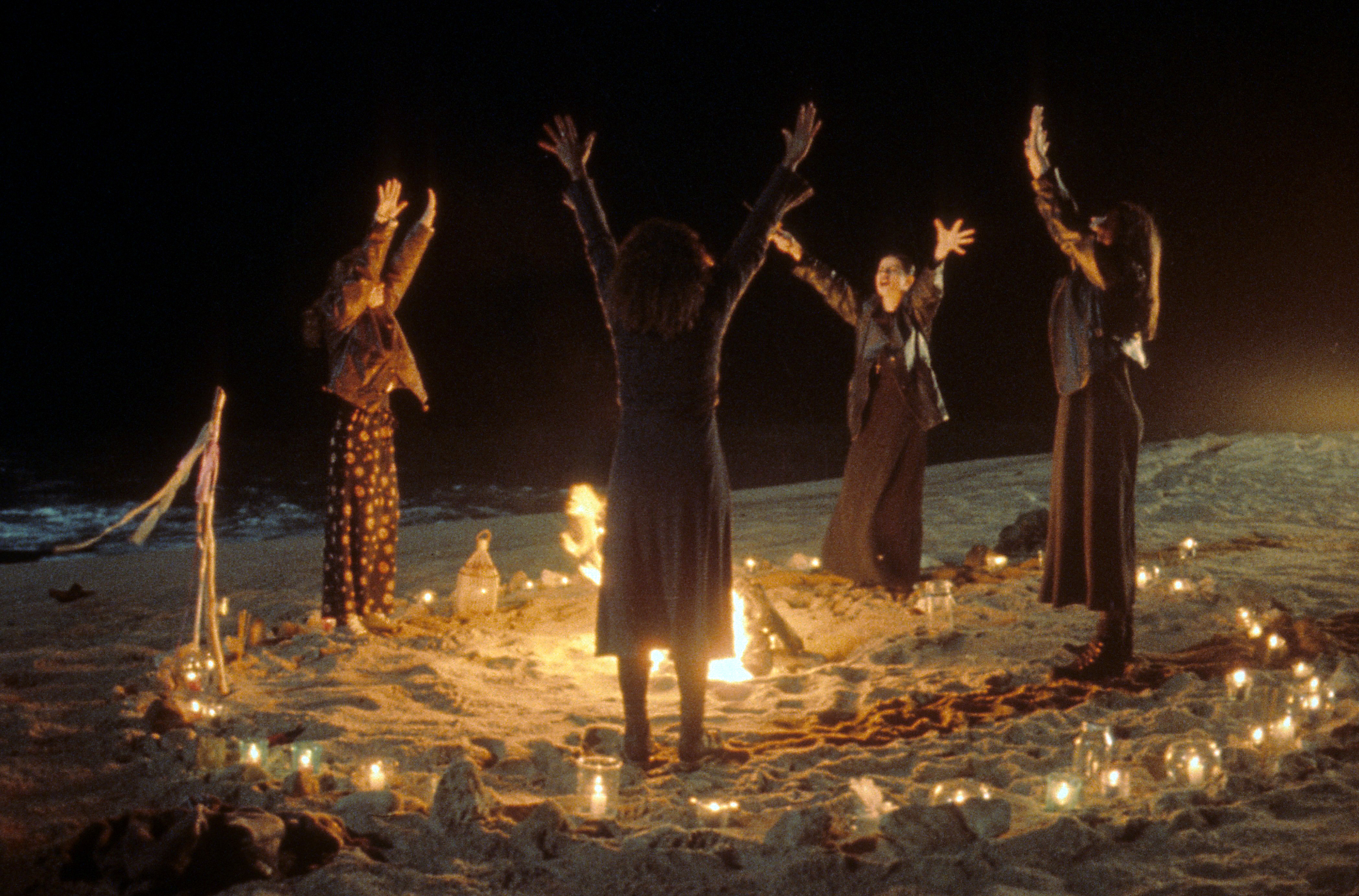 Robin Tunney, Fairuza Balk, Rachel True and Neve Campbell crowded around a fire, performing a ritual in a scene from the film 'The Craft', 1996.