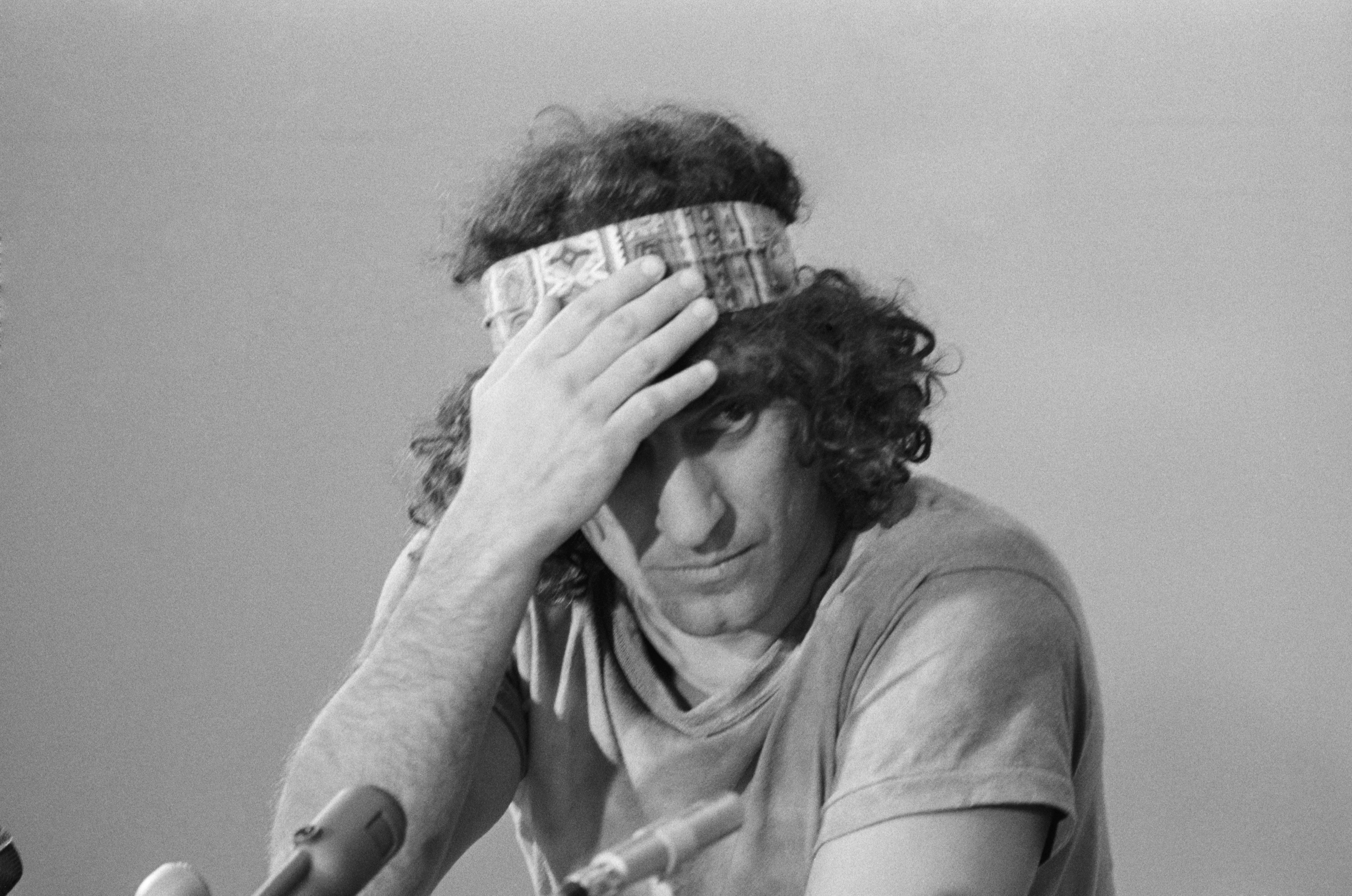 Abbie Hoffman adjusts his headband during a news conference about the trial