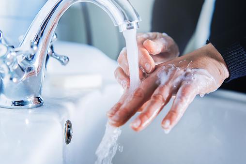Woman washing hands at home