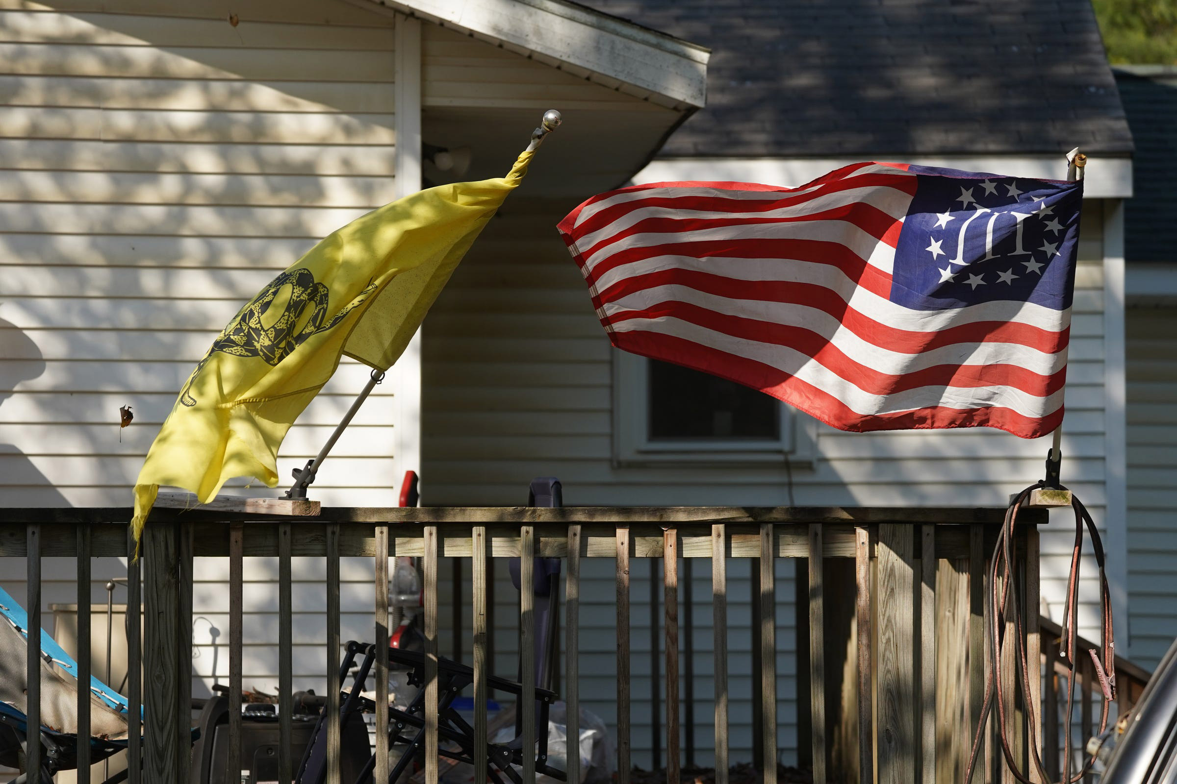 A Three Percenter flag and a Gadsden Flag fly onthe home of Michael Null in Plainwell, Mich., on October 9, 2020. Null one of 13 suspects accused of plotting to abduct and possibly harm Michigan Gov. Gretchen Whitmer.