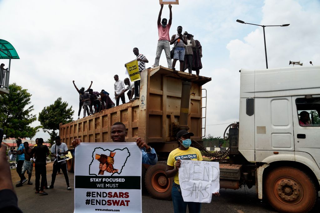 Protesters stand with banners on a truck forced to barricade the Lagos-Ibadan expressway during a demonstration to protest against police brutality and scrapping of Special Anti-Robbery Squad (SARS) in Lagos, on October 15, 2020.