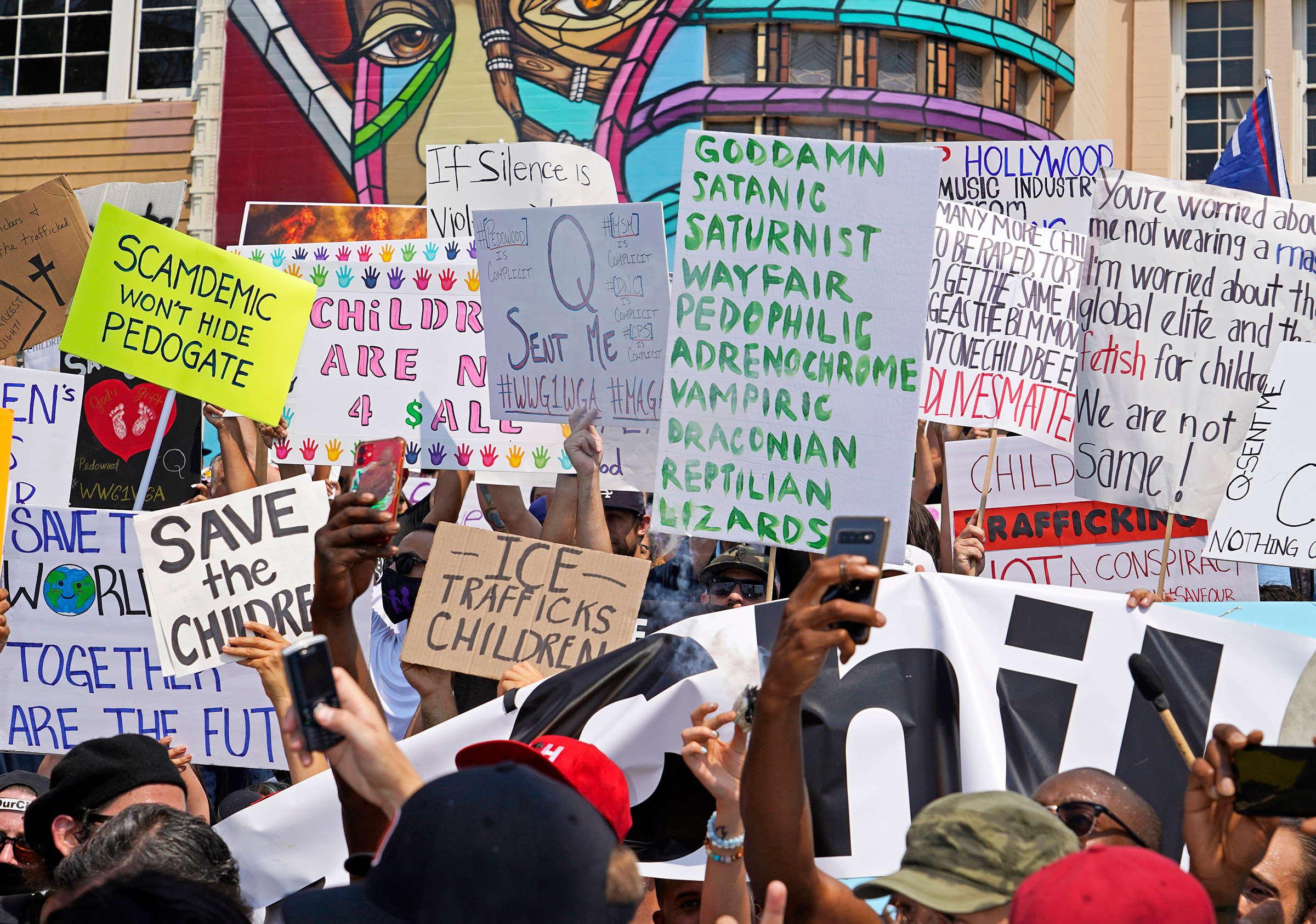 Signs showing various conspiracy theories at a Save Our Children rally in Los Angeles, Aug. 22, 2020.