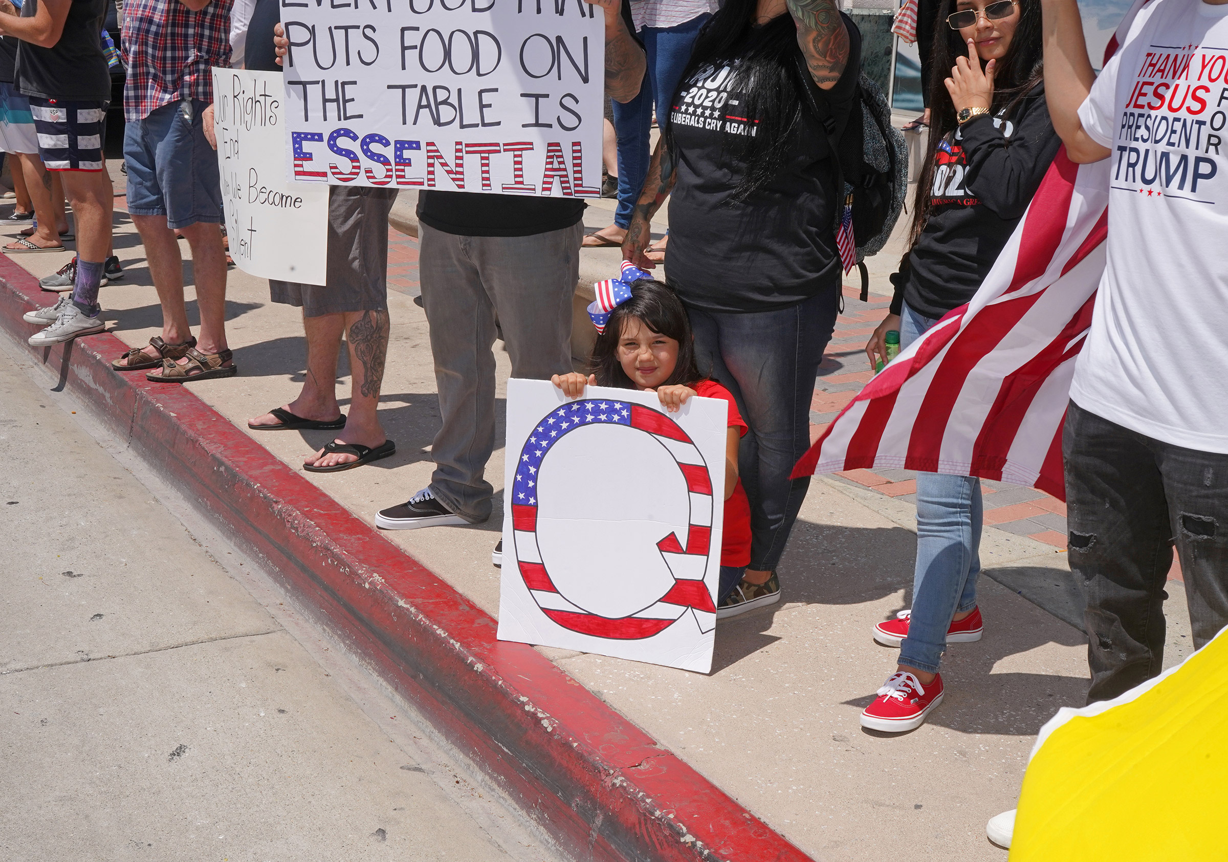 A child with a QAnon sign at an anti-lockdown rally in Huntington Beach, Calif., May 1, 2020.