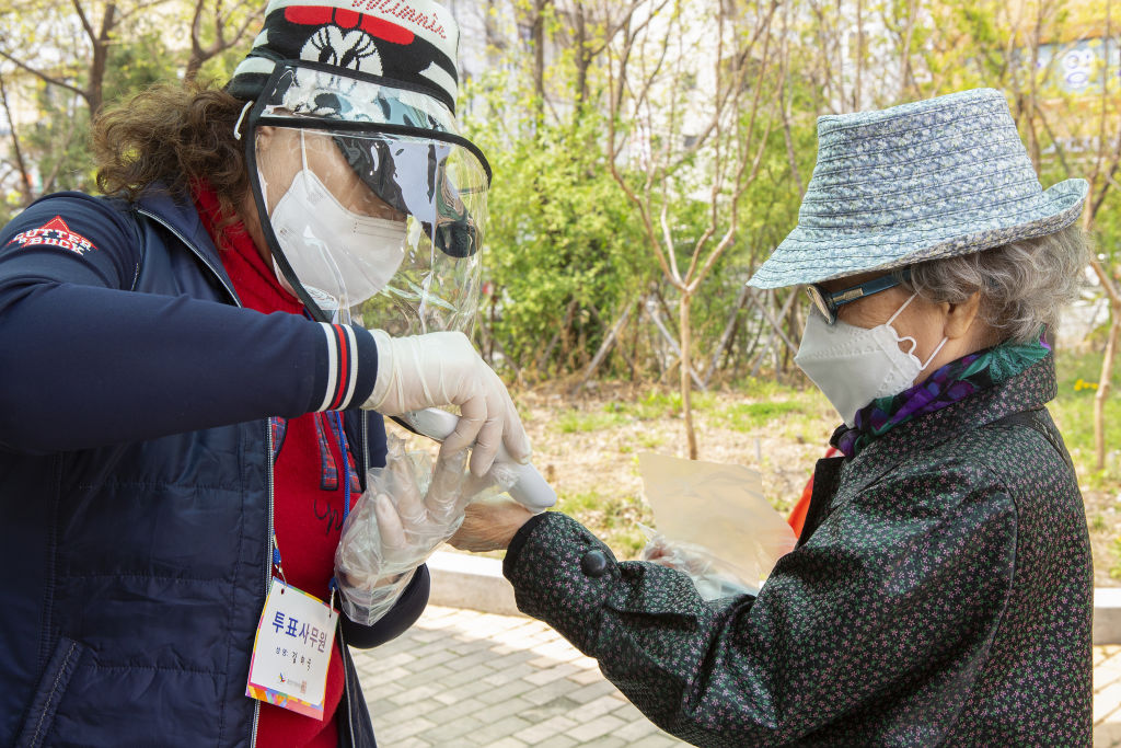 A poll worker wearing a medical mask and plastic gloves checks the body temperature of a citizen South Korean citizen, at a polling station at the country's general election amid the coronavirus outbreak in Seoul on April 15, 2020.