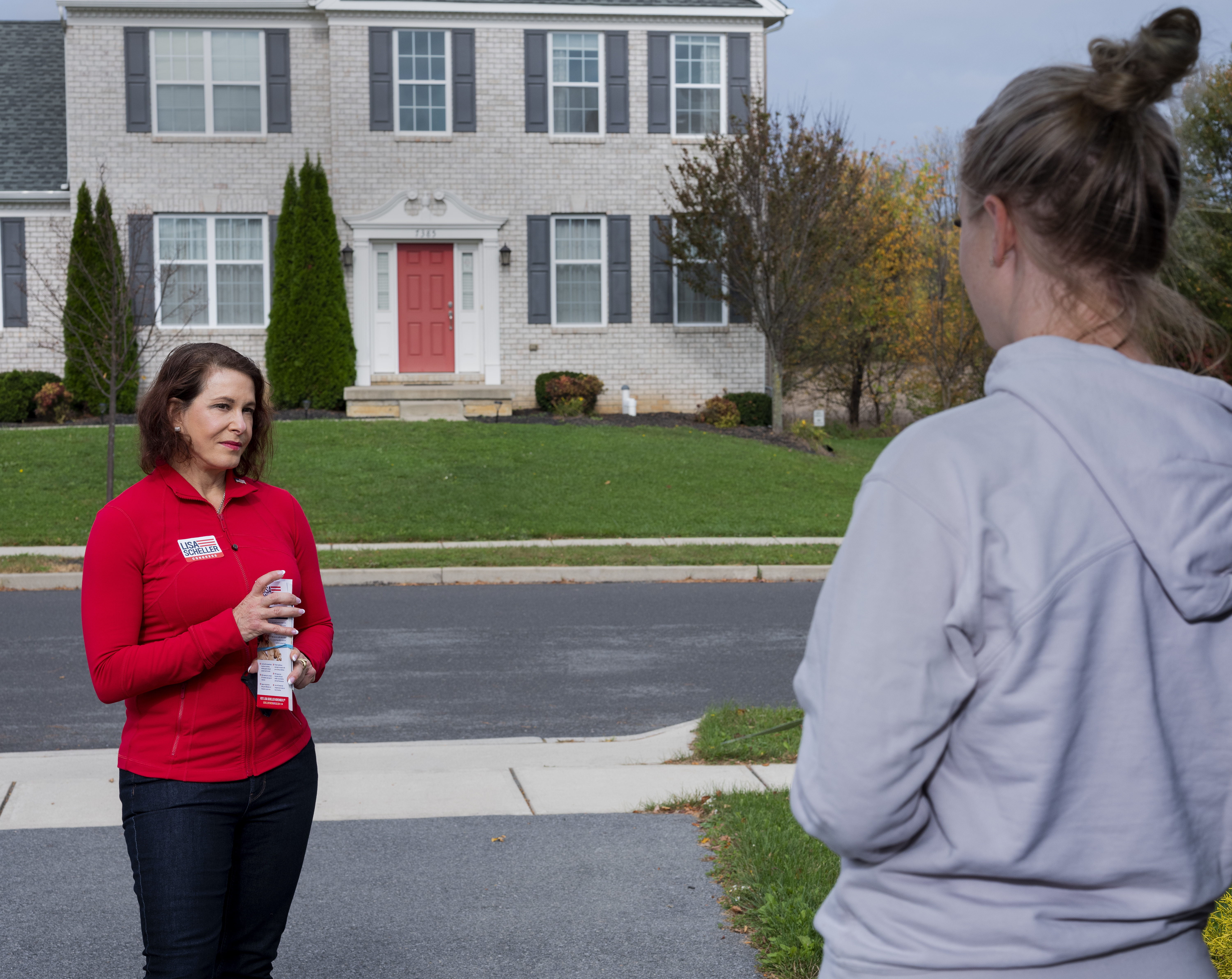 Republican nominee, Lisa Scheller, speaks with a resident while canvasing in Allentown, Pa., on Oct. 24, 2020.