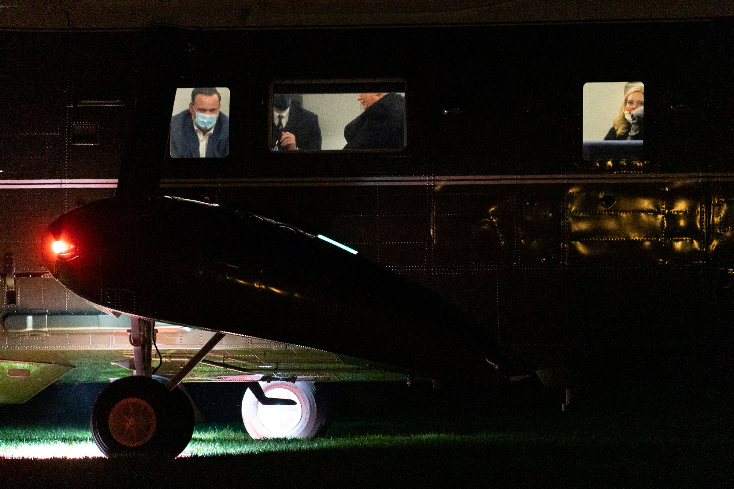 President Donald Trump, center, is seen seated inside Marine One helicopter, not wearing a face mask, as he and members of his staff, including White House director of social media Dan Scavino, left, arrive at the White House in Washington D.C., on Oct. 1, 2020. President Trump and first lady Melania Trump have tested positive for the coronavirus, the president tweeted early Friday.