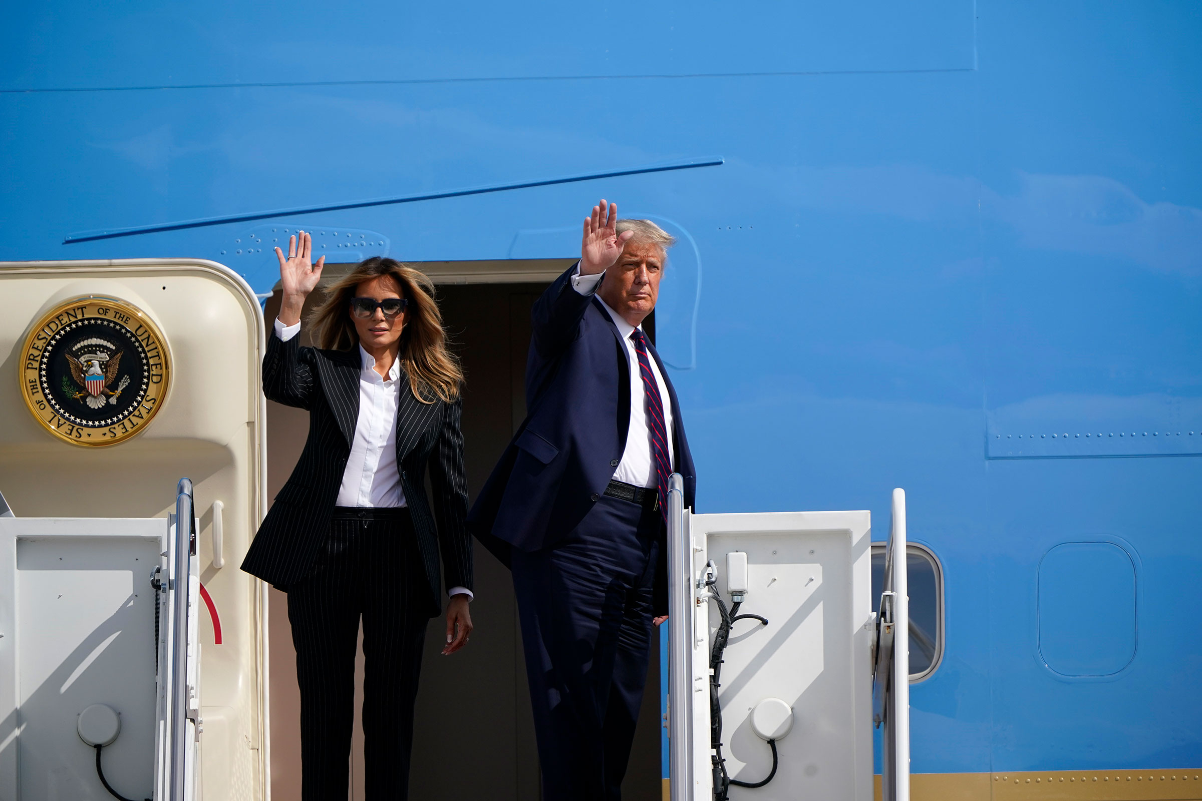 President Donald Trump and first lady Melania Trump wave before boarding Air Force One at Andrews Air Force Base, Md to travel to the first presidential debate on Sept. 29, 2020.