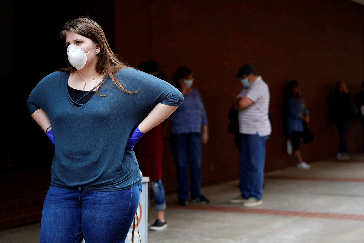 A woman who lost her job waits in line to file for unemployment following an outbreak of the coronavirus, at an Arkansas Workforce Center in Fort Smith, Ark., April 6, 2020.