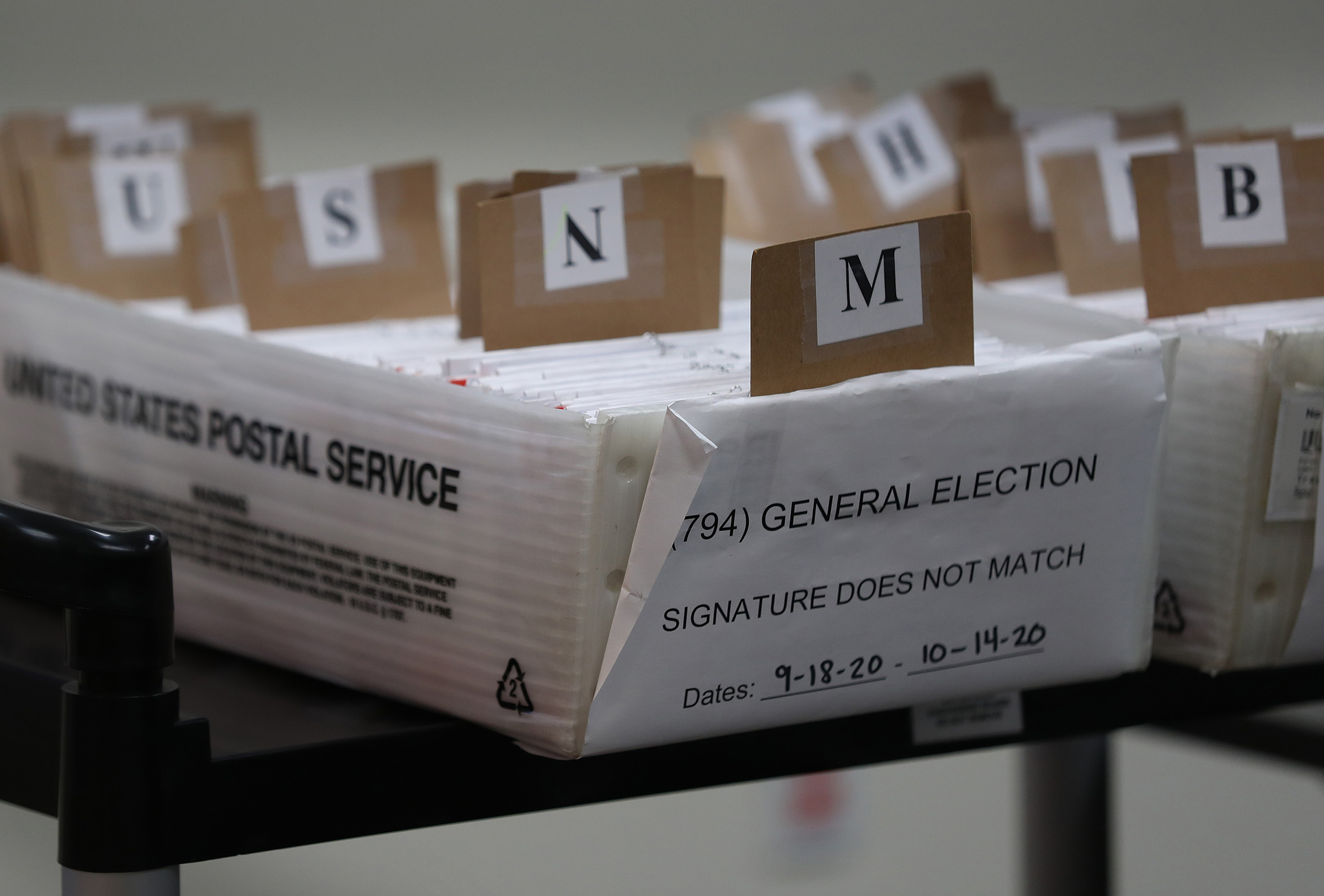 Boxes for Vote-by-Mail ballots that need to be reviewed due to signature discrepancies are seen ahead of the Nov. 3 general election at the Miami-Dade County Elections Department on Oct. 15 in Doral, Fla.