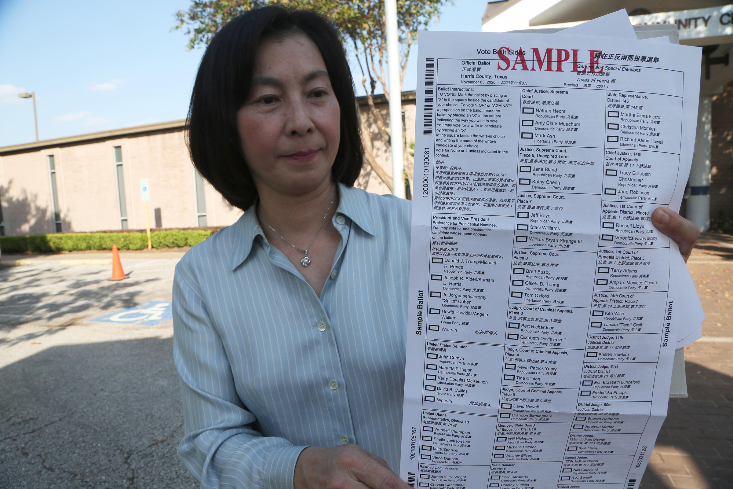 A woman presents a Chinese ballot sample for the 2020 presidential election at a polling station near Chinatown on Oct. 14 in Houston