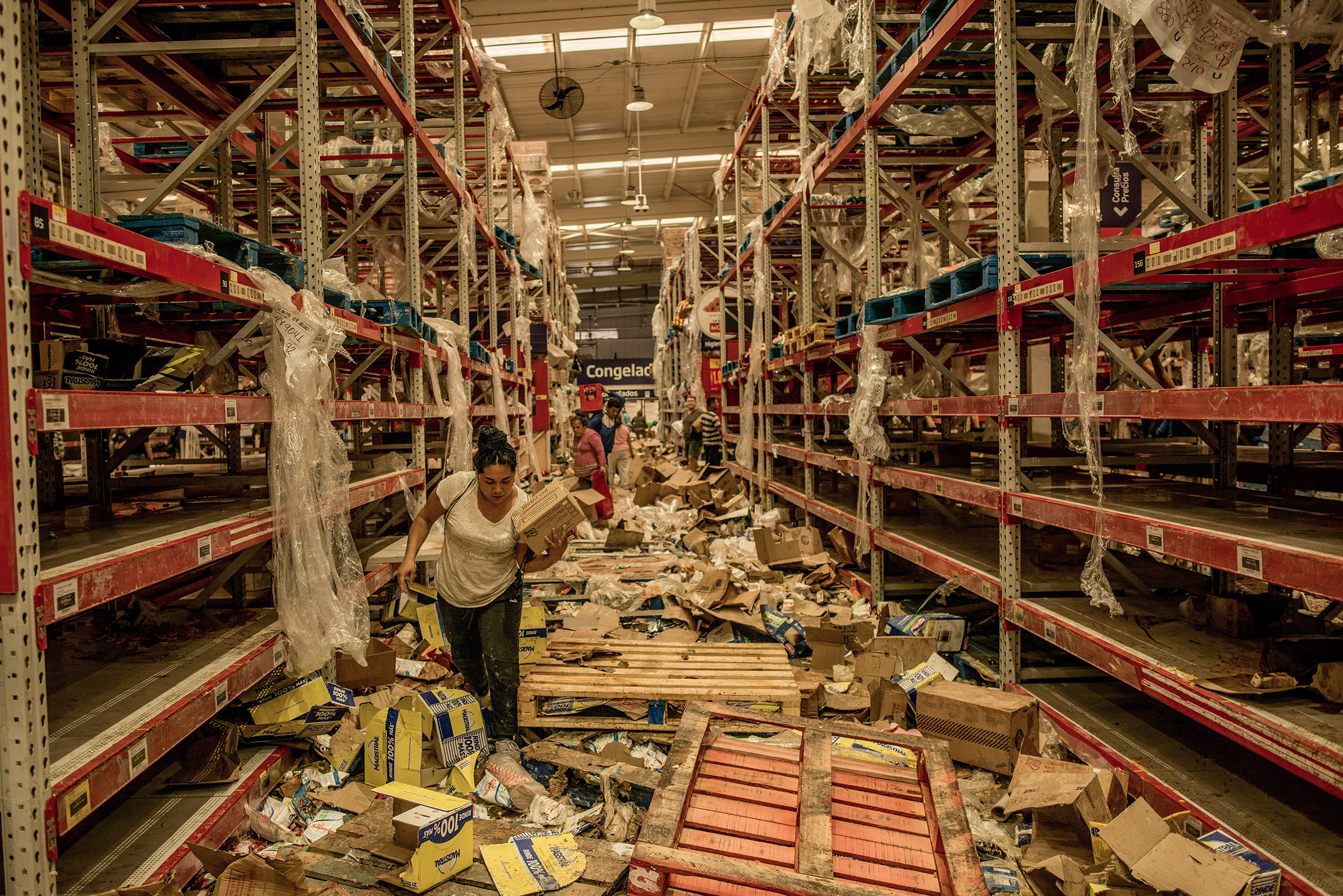 People look through the remains of a looted supermarket in Santiago, Chile, on Oct. 23, 2019.