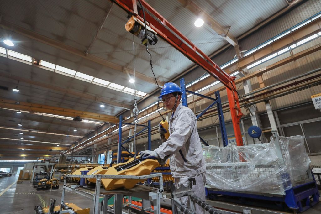 An employee works on the assembly line of construction machinery at a workshop of Shandong Lingong Construction Machinery Co. on October 15, 2020 in Linyi, Shandong Province of China.