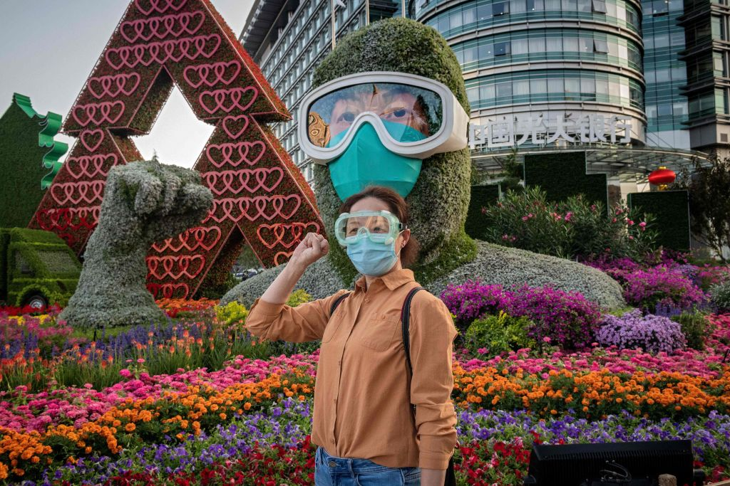 A woman poses for a photo in front of a flower display dedicated to frontline healthcare workers during the Covid-19 pandemic in Beijing, China on Sept. 29, 2020.