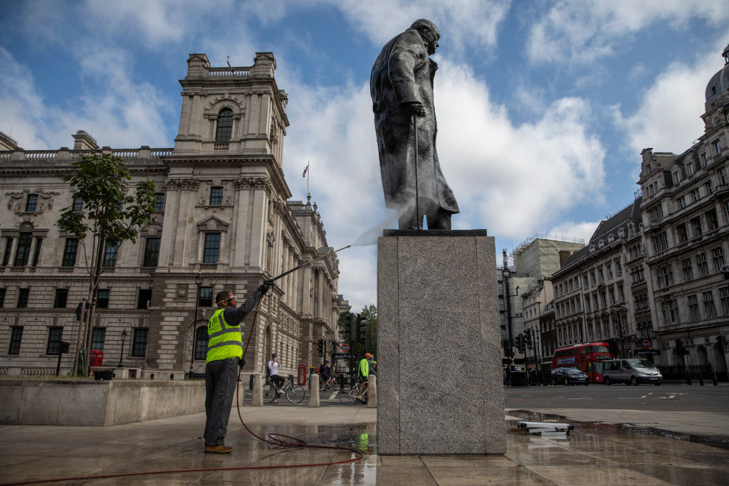 A worker cleans the Churchill statue in Parliament Square that had been spray painted with the words 'was a racist' on June 8, 2020 in London.