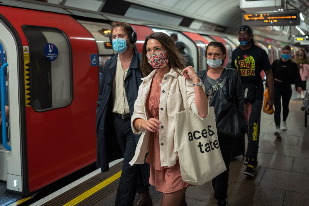 Commuters wearing protective face coverings travel on Victoria line at rush hour in central London on September 23, 2020.