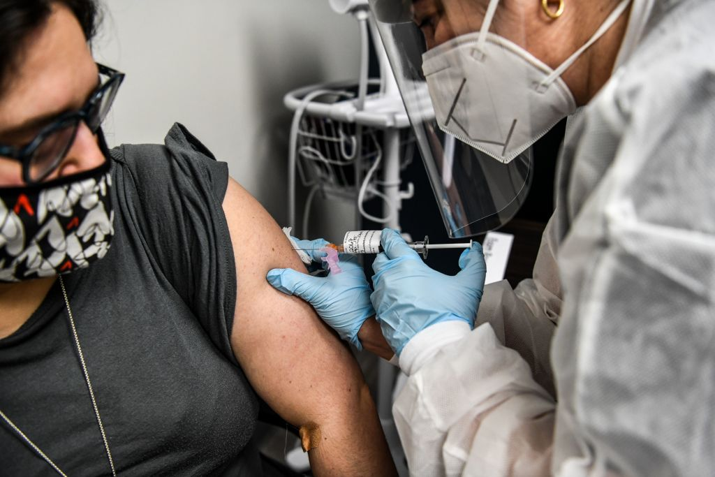 Heather Lieberman (L), 28, receives a COVID-19 vaccination from Yaquelin De La Cruz at the Research Centers of America in Hollywood, Florida, on August 13, 2020.