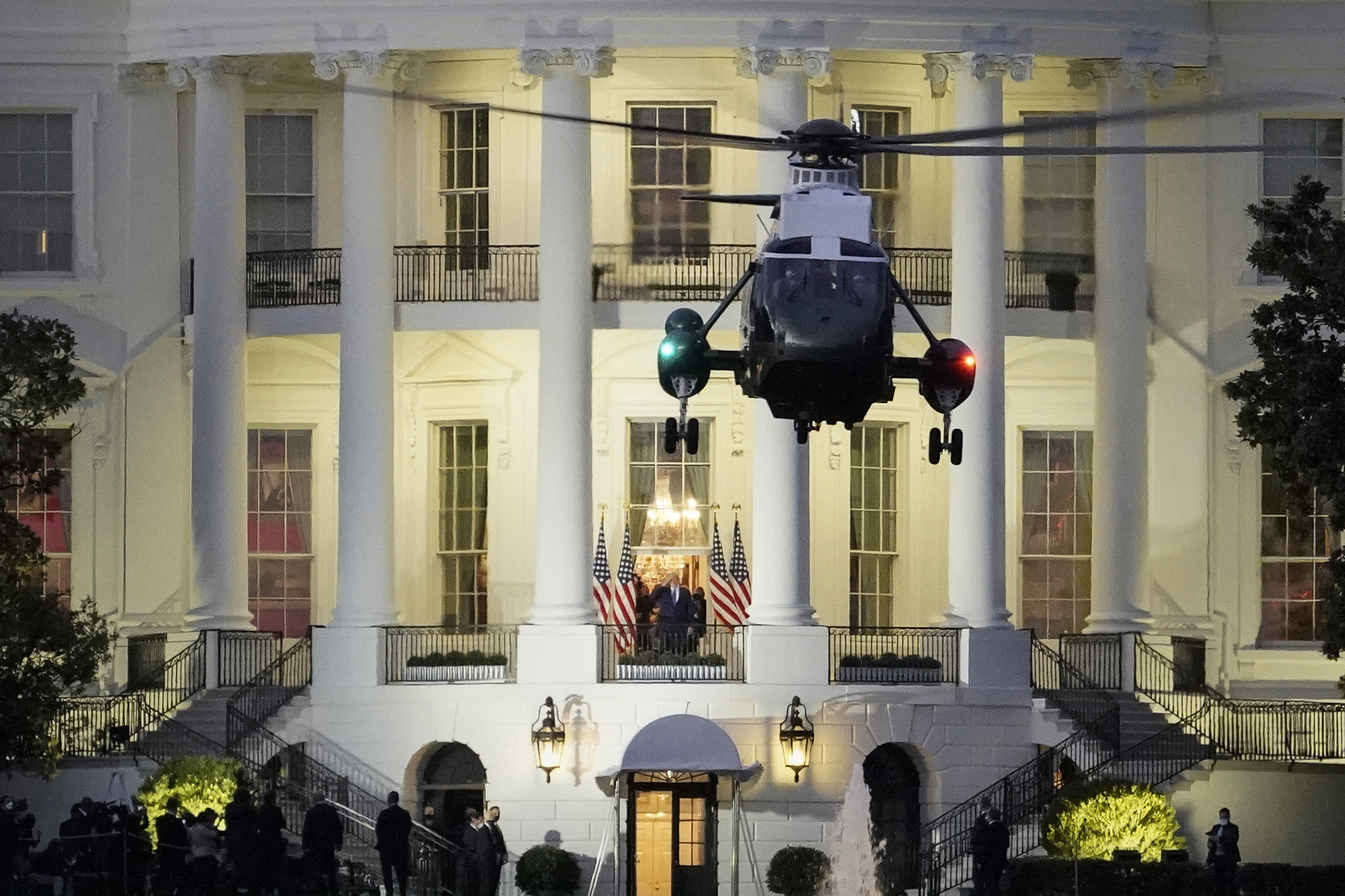 U.S. President Donald Trump stands on the Blue Room Balcony as Marine One takes off from the South Lawn of the White House on Oct. 5