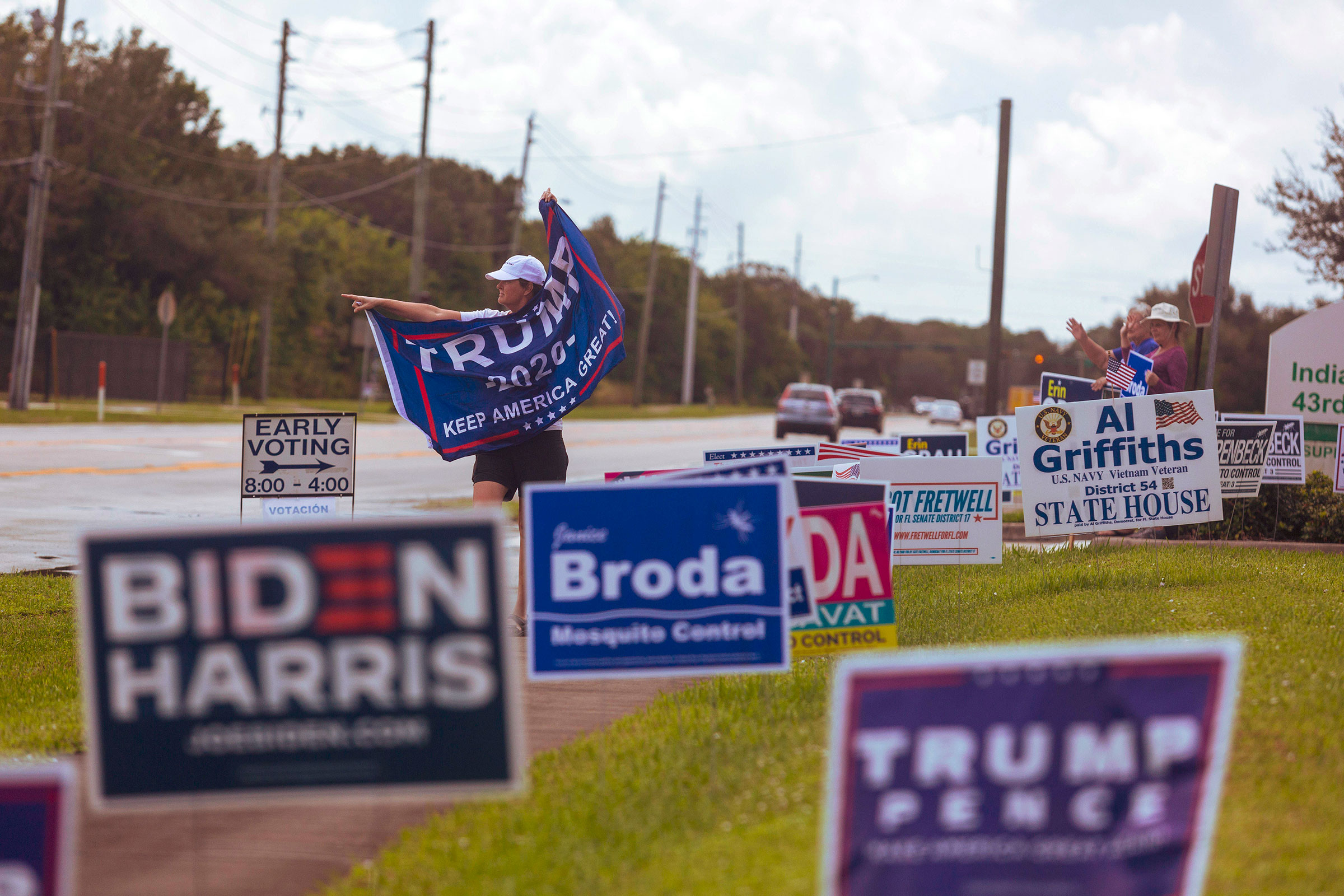 A person waves a Trump flag near a polling place in Vero Beach, Fla.,on Oct. 23, 2020.