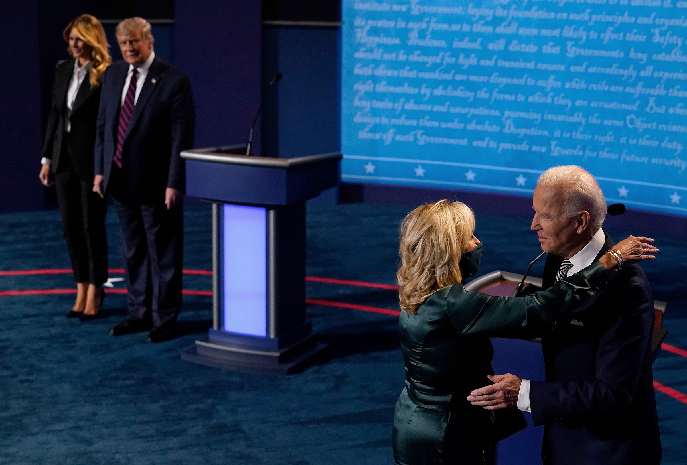 First Lady Melania Trump and President Donald Trump look on as Democratic presidential candidate and former Vice President Joe Biden hugs his wife, Jill Biden, after the first presidential debate in Cleveland on Sept. 29, 2020.