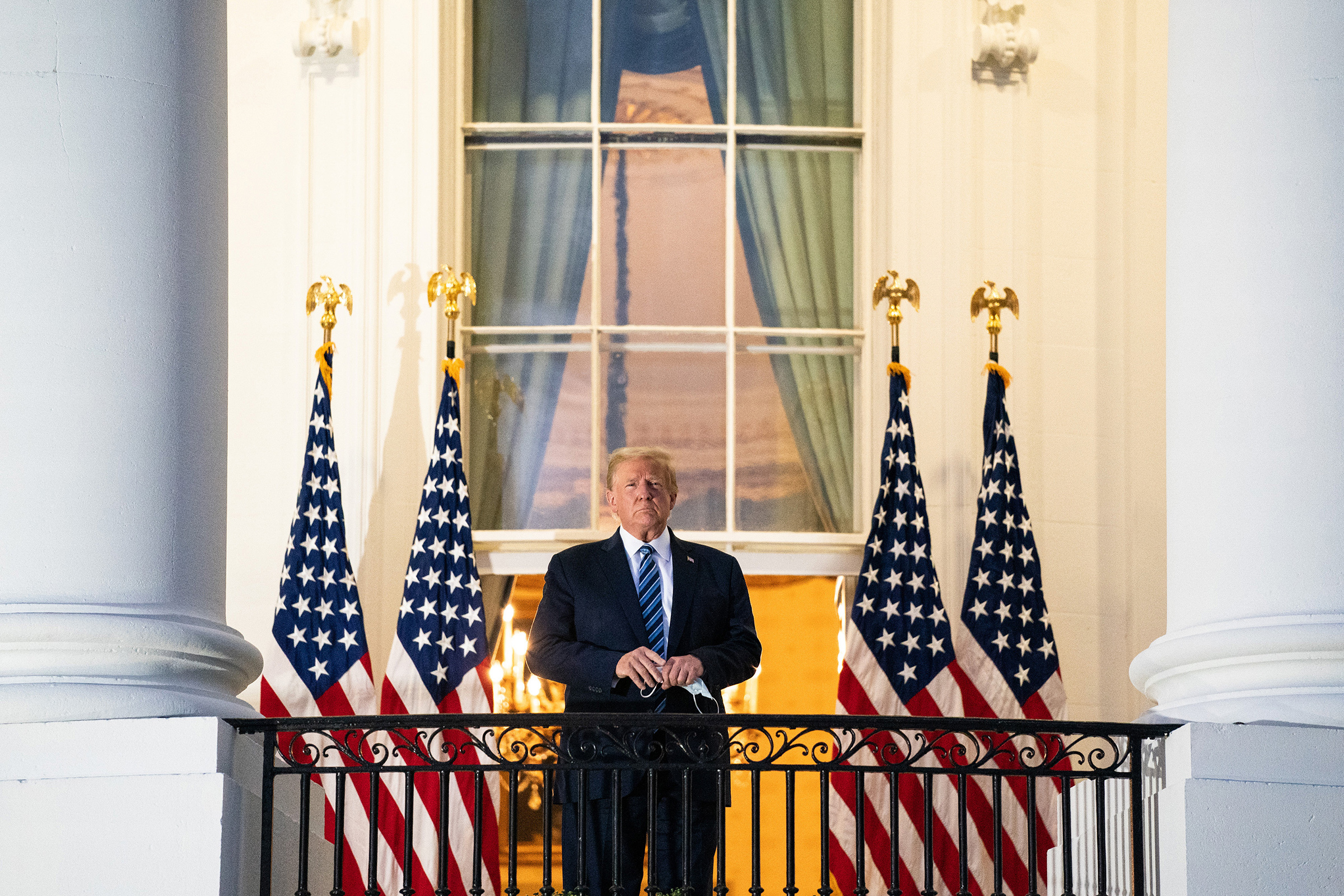 President Donald Trump stands on the Truman Balcony upon returning to the White House on Oct. 5 after testing positive for COVID-19 and spending four days at the the Walter Reed Medical Center in Bethesda, Md.