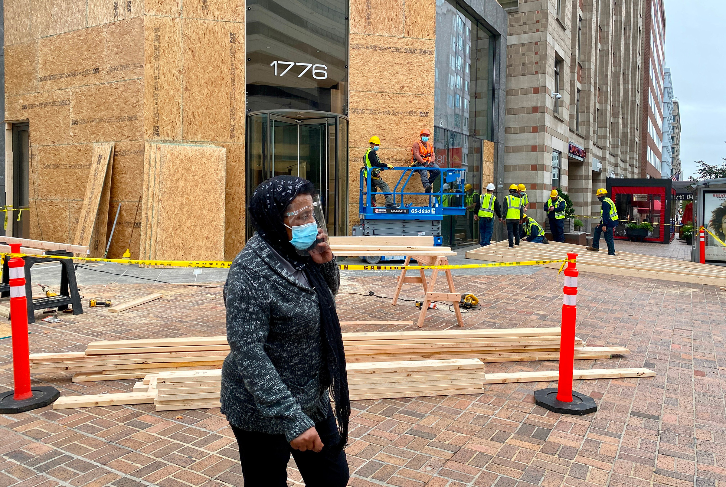 Workers install protections on building facades near the White House as building managers and local businesses fear violent demonstrations ahead of the coming Presidential elections, on Oct. 26
