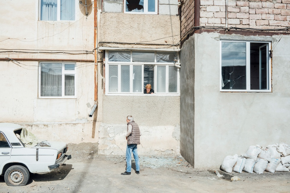 A woman speaks with a man through an open window of a shelled building in Stepanakert.
