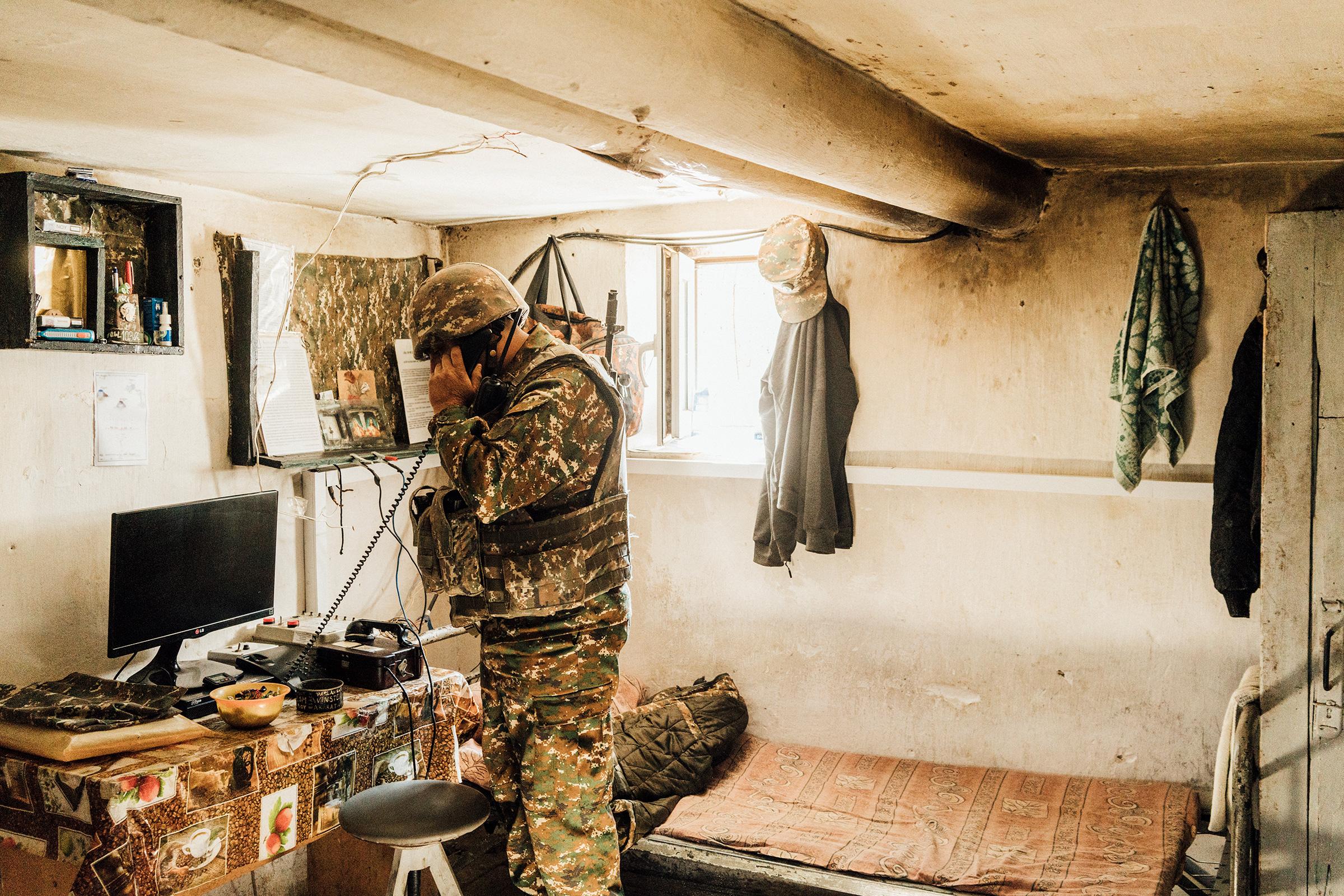 An Armenian soldier talks on a radio inside a bunker on a frontline position near Askeran.
