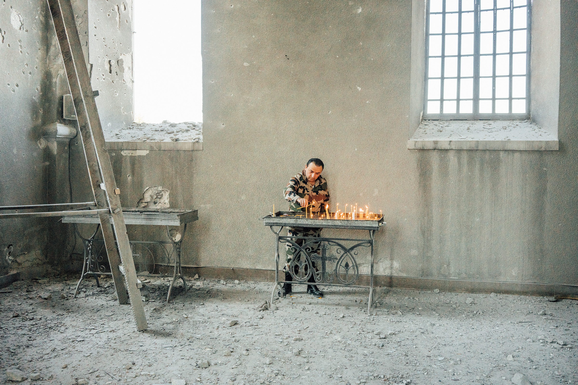 An Armenian soldier lights candles inside the Holy Savior Cathedral, which was damaged by shelling, in the town of Shusha outside Stepanakert.