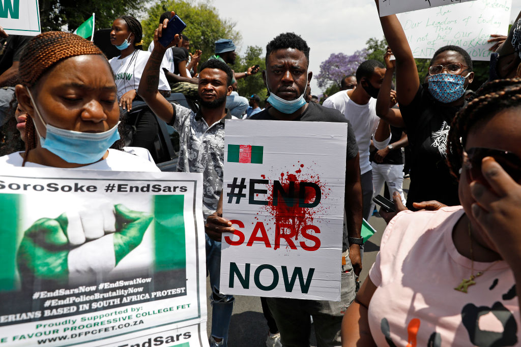 A Nigerian man based in South Africa holds a poster reading  #EndSARSNow  during a protest outside their embassy in Pretoria on Oct. 21, 2020 in solidarity with Nigerian youth.