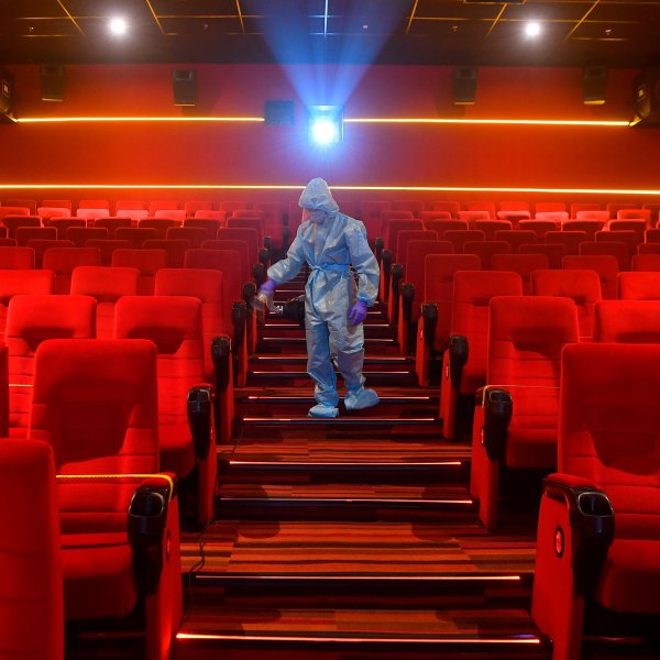 A worker sanitizes the inside of a movie theater ahead its reopening in Mumbai, October 13, 2020.