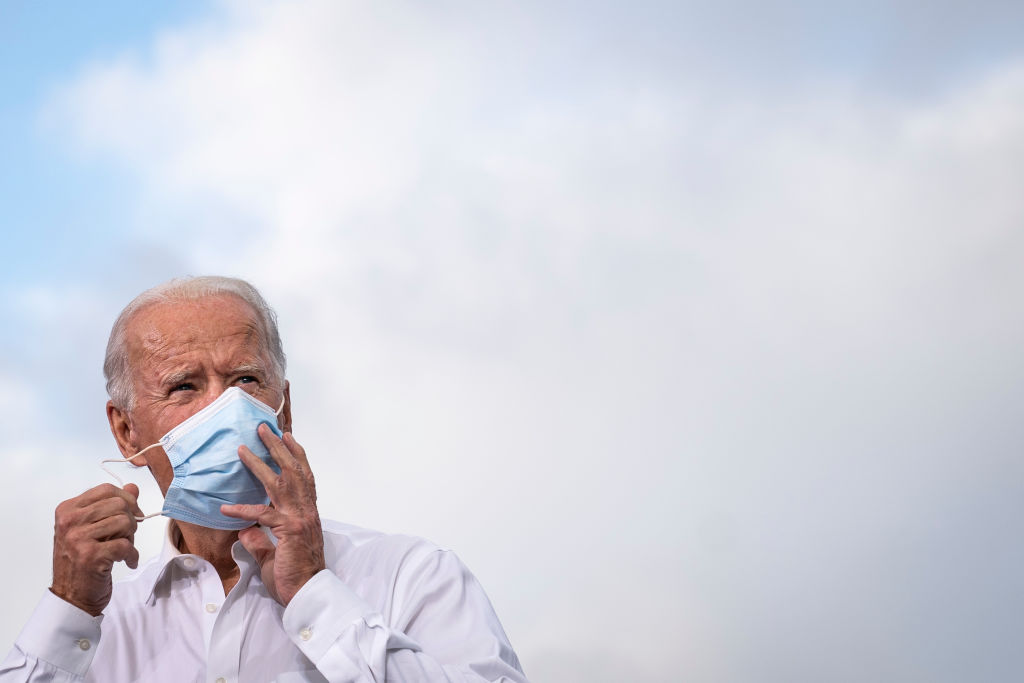 Democratic presidential nominee Joe Biden takes off his face mask before speaking during a drive-in campaign rally in Atlanta on October 27, 2020.