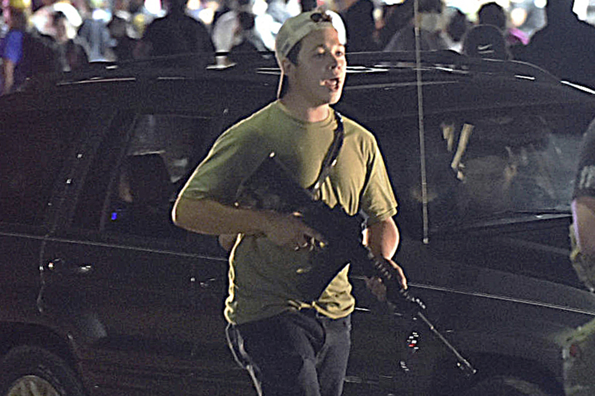 In this Tuesday, Aug. 25, 2020, file photo, Kyle Rittenhouse carries a weapon as he walks along Sheridan Road in Kenosha, Wis., during a night of unrest following the weekend police shooting of Jacob Blake.