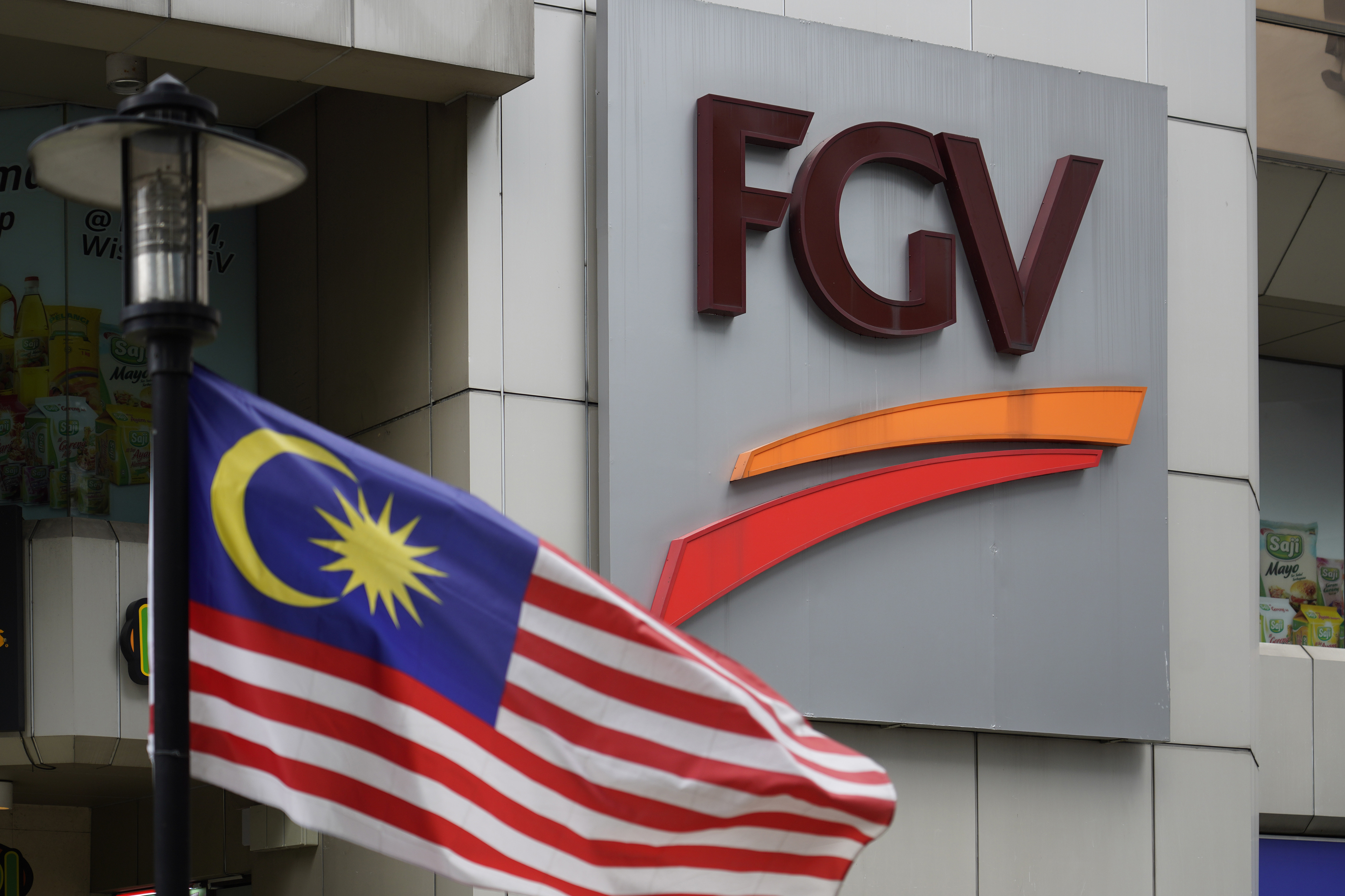 """A Malaysian national flag is on display outside FGV Holdings Berhad, one of Malaysia's largest palm oil companies, in Kuala Lumpur, Thursday, Oct. 1, 2020. Malaysian palm oil producer FGV Holdings Berhad vowed Thursday to """"clear its name"""" after the U.S. banned imports of its palm oil over allegations of forced labor and other abuses."""
