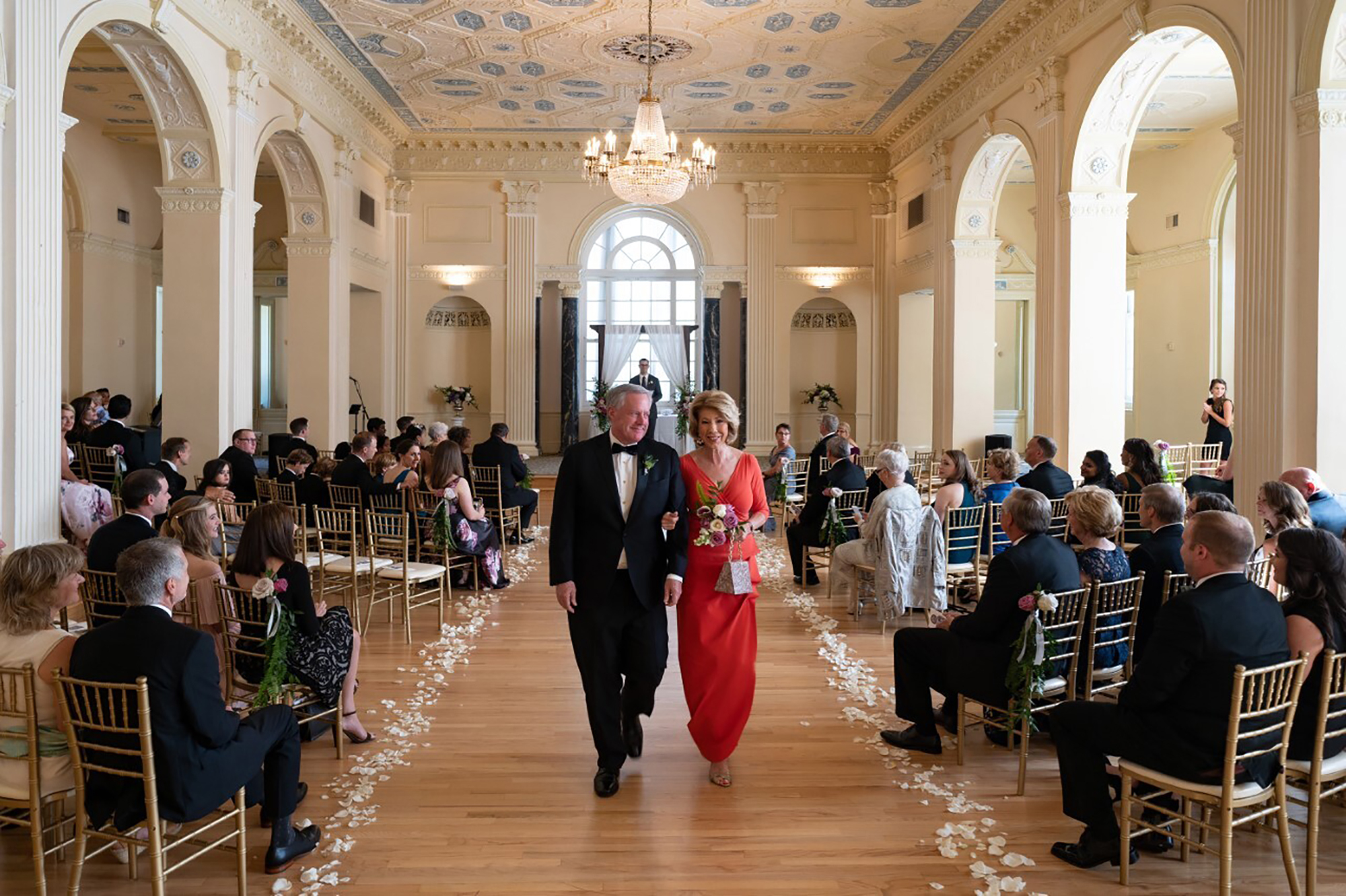 In this photo provided by Ember Studio, White House Chief of Staff Mark Meadows and his wife, Debbie Meadows, walk down the aisle at their daughter's wedding, Sunday, May 31, 2020, in Atlanta.