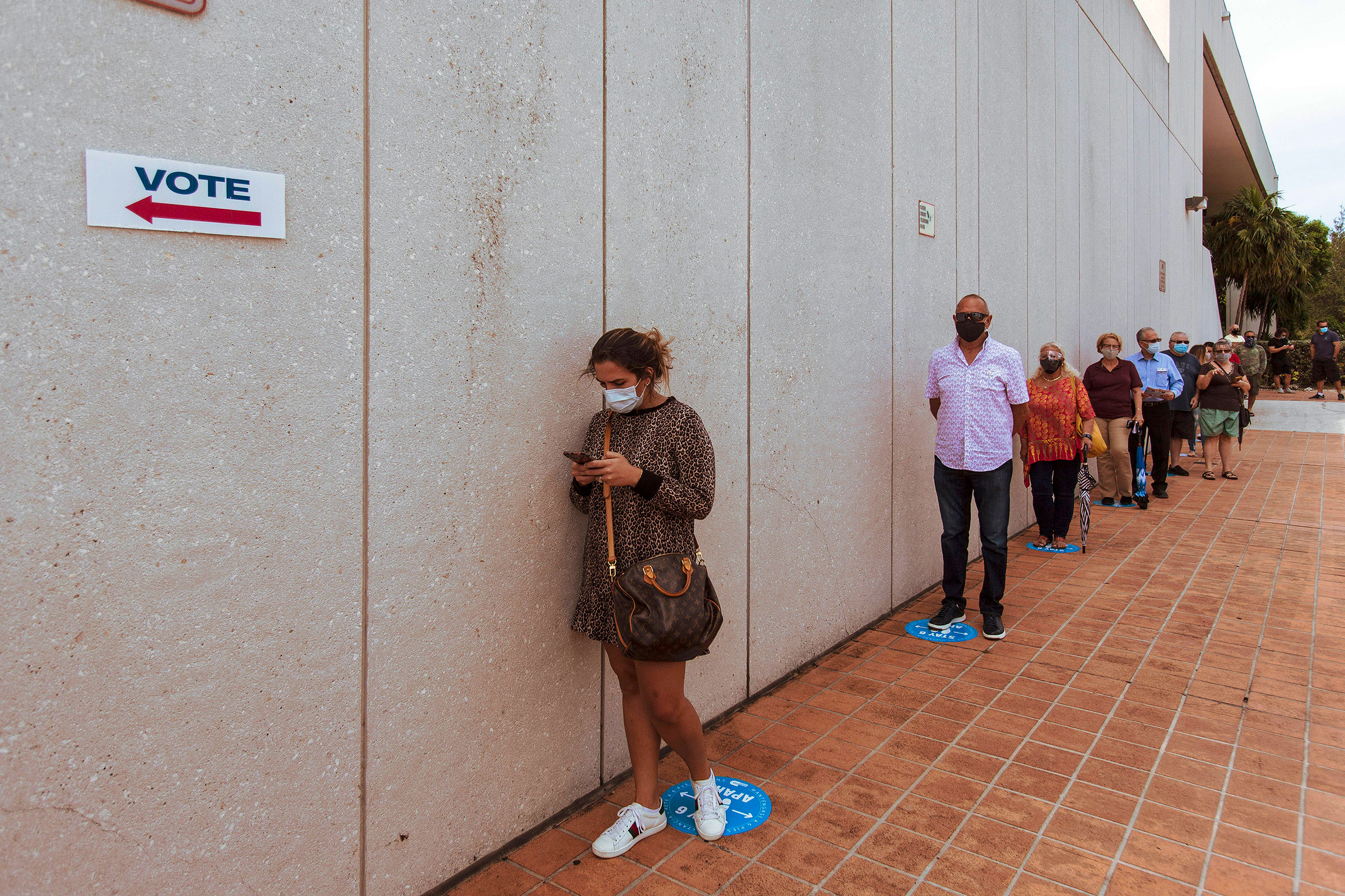 People wait on line to cast their ballot on the first day of early voting at a polling place in Miami, Fla., Oct. 19, 2020.