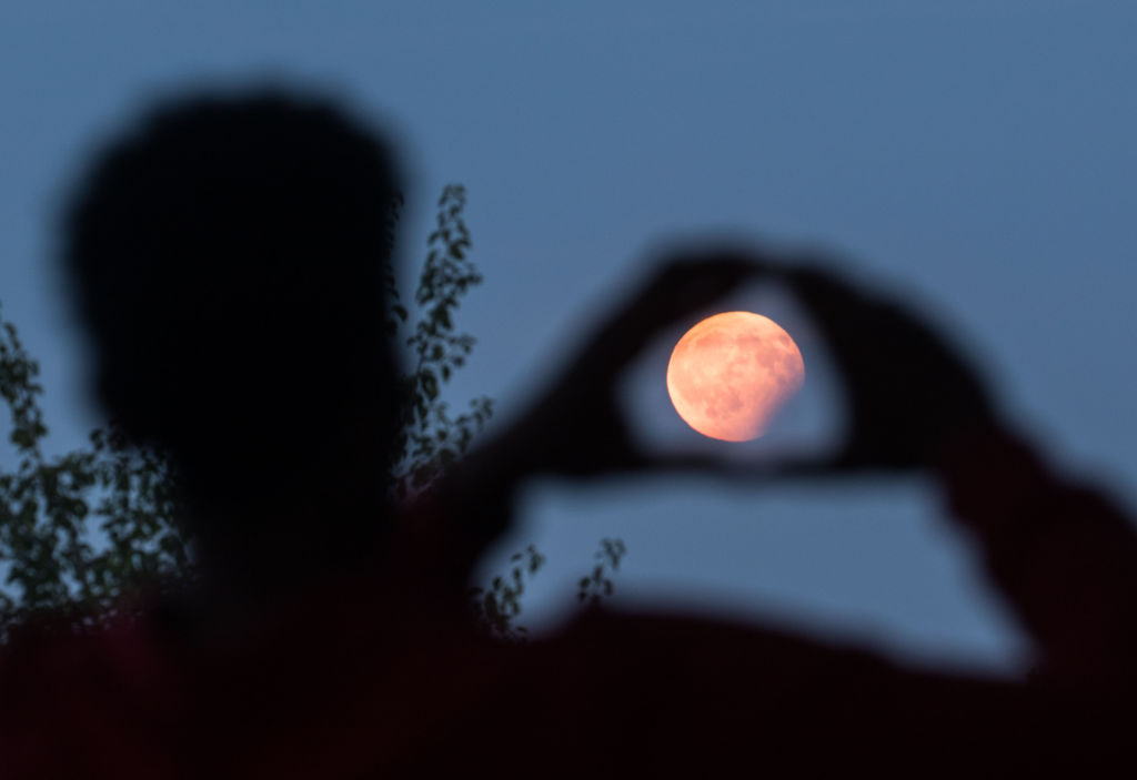A man frames with his hands the moon standing in a partial lunar eclipse on August 7, 2017 in Frankfurt am Main, western Germany.