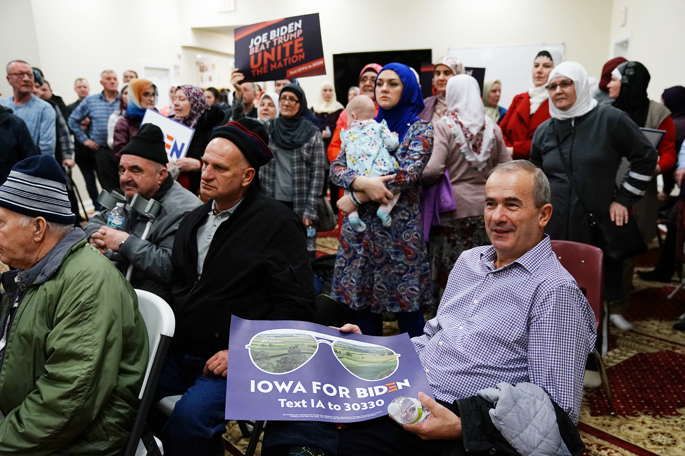 Participants hold campaign signs for Vice President Joe Bidenduring the first-in-the-nation Iowa caucus at the Islamic and Education Center Ezan mosque in Des Moines, Iowa on Feb. 3, 2020.