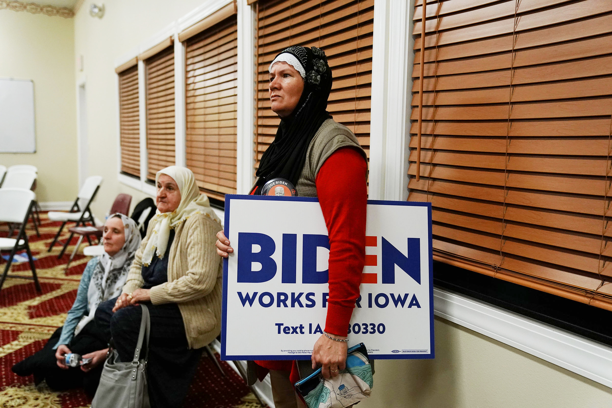 A participant holds a campaign sign for Biden during the first-in-the-nation Iowa caucus in Des Moines.