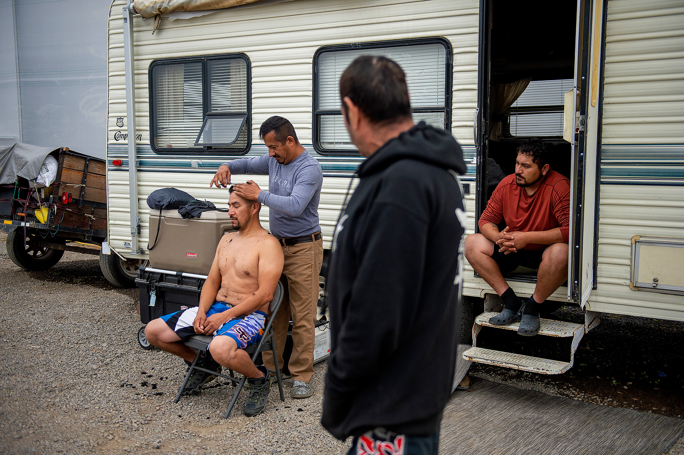 Julio Hernandez cuts the hair of his brother, Alvaro Hernandez, at a farm that opened space to people displaced by wildfires in Central Point, Ore., on Sept. 26, 2020. The Almeda Fire leveled some of the only affordable housing for the immigrants who work the fields, kitchens and construction sites of southern Oregon.