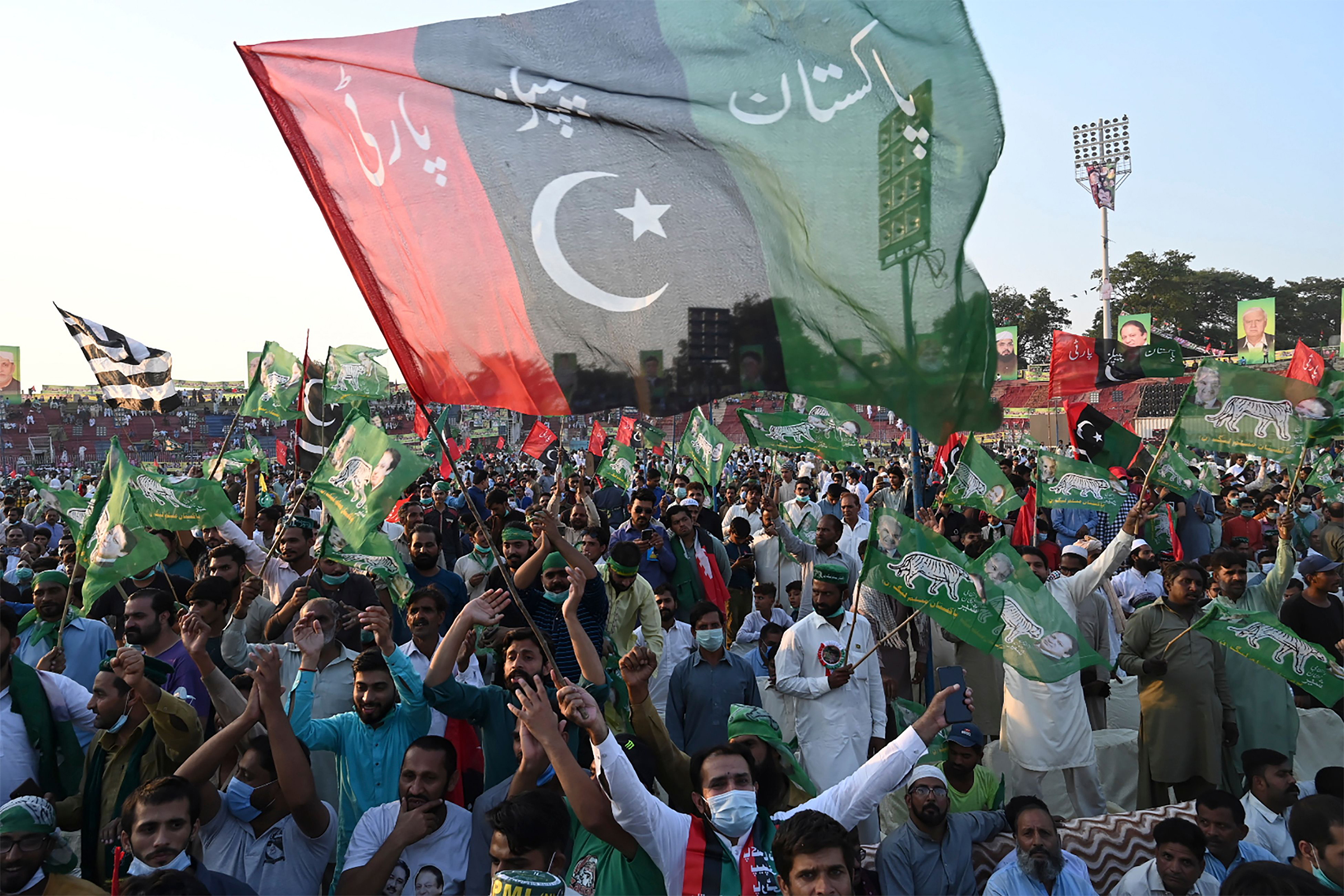 Activists of the newly-formed Pakistan Democratic Movement (PDM), an opposition alliance of 11 parties, wave parties flags during the first public rally in the eastern city of Gujranwala on Oct. 16, 2020.