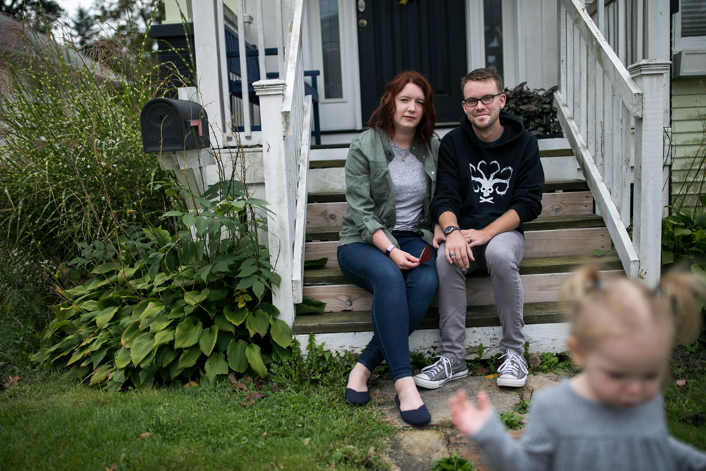 Shelby Parker sits outside of her home with her husband Ben and daughter Abby in Cuyahoga Falls, Ohio on Oct. 3. Parker planned to get pregnant this year but is contemplating not trying for a second child at all now due to the coronavirus pandemic.