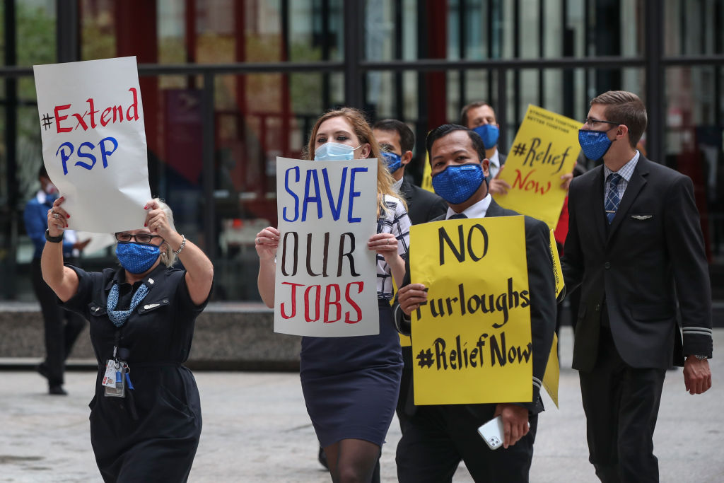 Airline industry workers hold signs during a protest in Federal Plaza in Chicago, Illinois, on September 9, 2020.