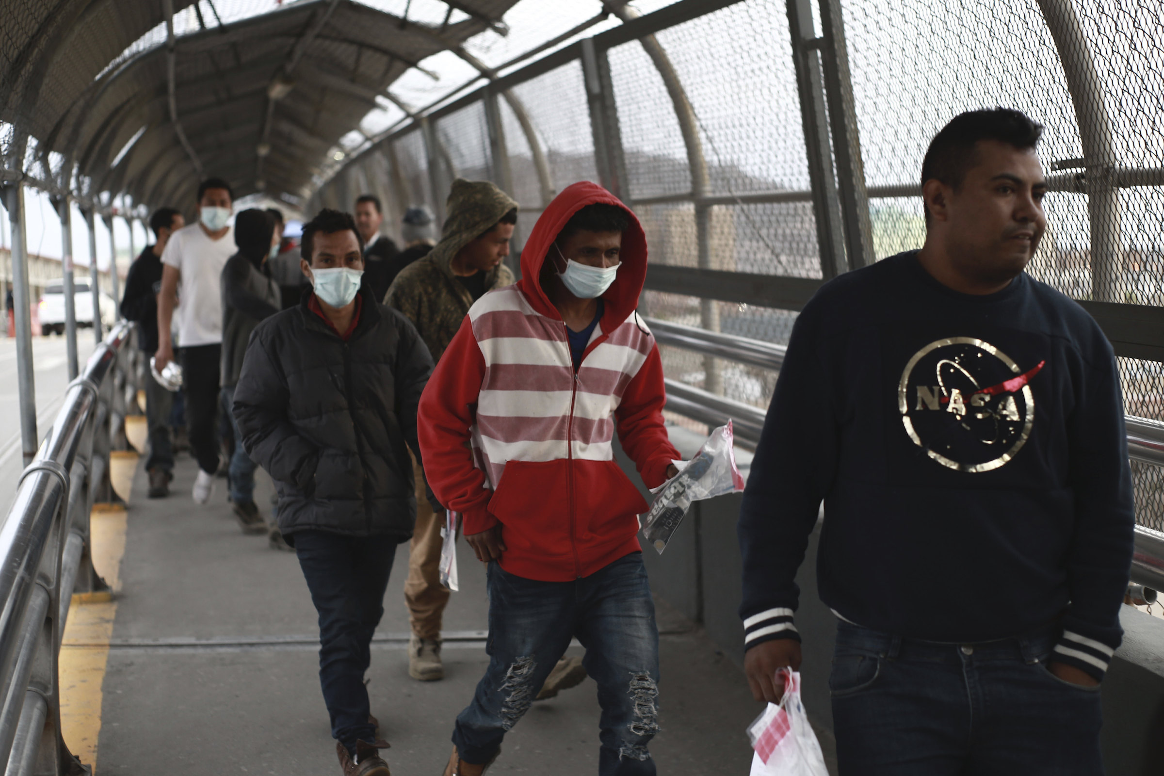 Central American migrants seeking asylum, some wearing protective face masks, return to Mexico via the international bridge at the U.S-Mexico border that joins Ciudad Juarez and El Paso on March 21, 2020.