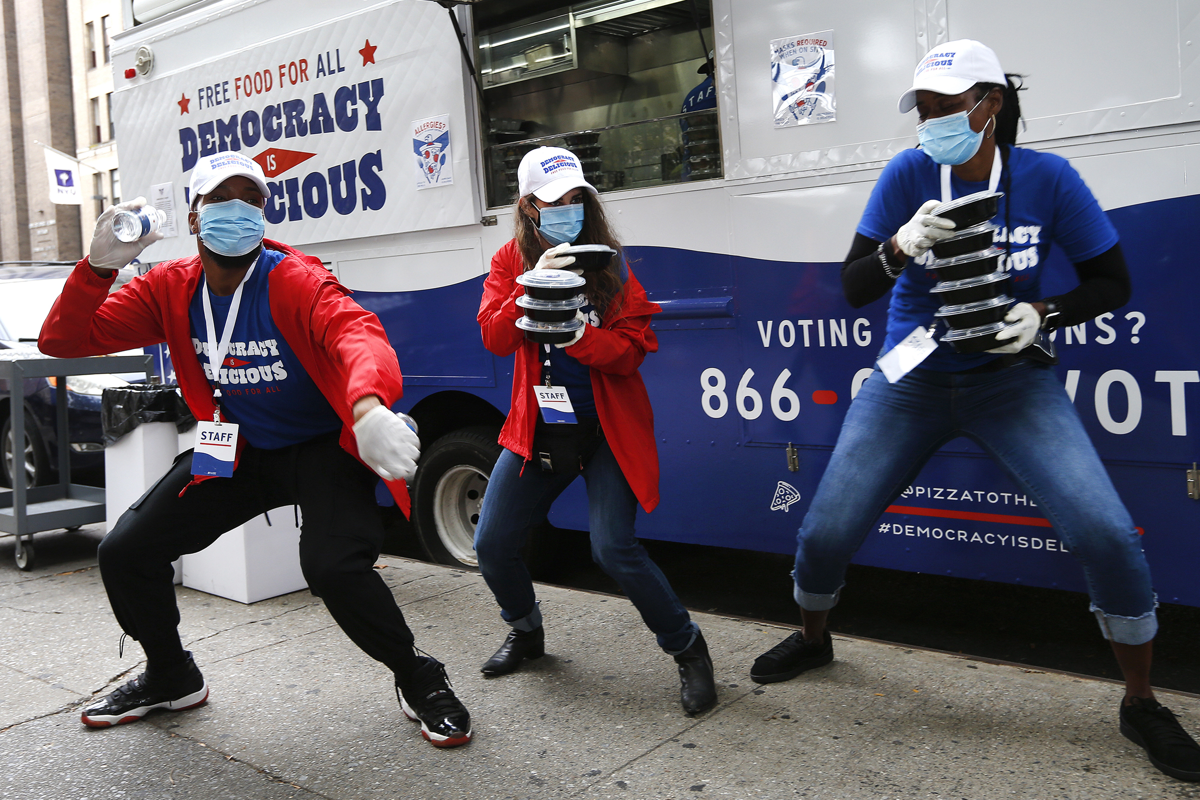 Pizza to the Polls food truck staff dance and spread good energy to voters waiting in line on early voting day in New York, on Oct. 24, 2020.