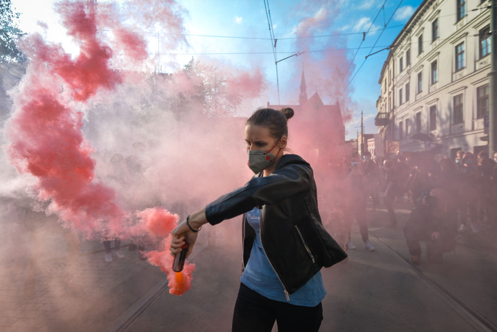 A Pro-Choice activist holds a smoke flare during a protest in Krakow's Market Square. Women's rights activists and their supporters staged their seventh day of protests in Krakow and all over Poland, opposing pandemic restraint, to express their anger at the ruling of Polish Supreme Court, which tightened the already strict abortion laws.