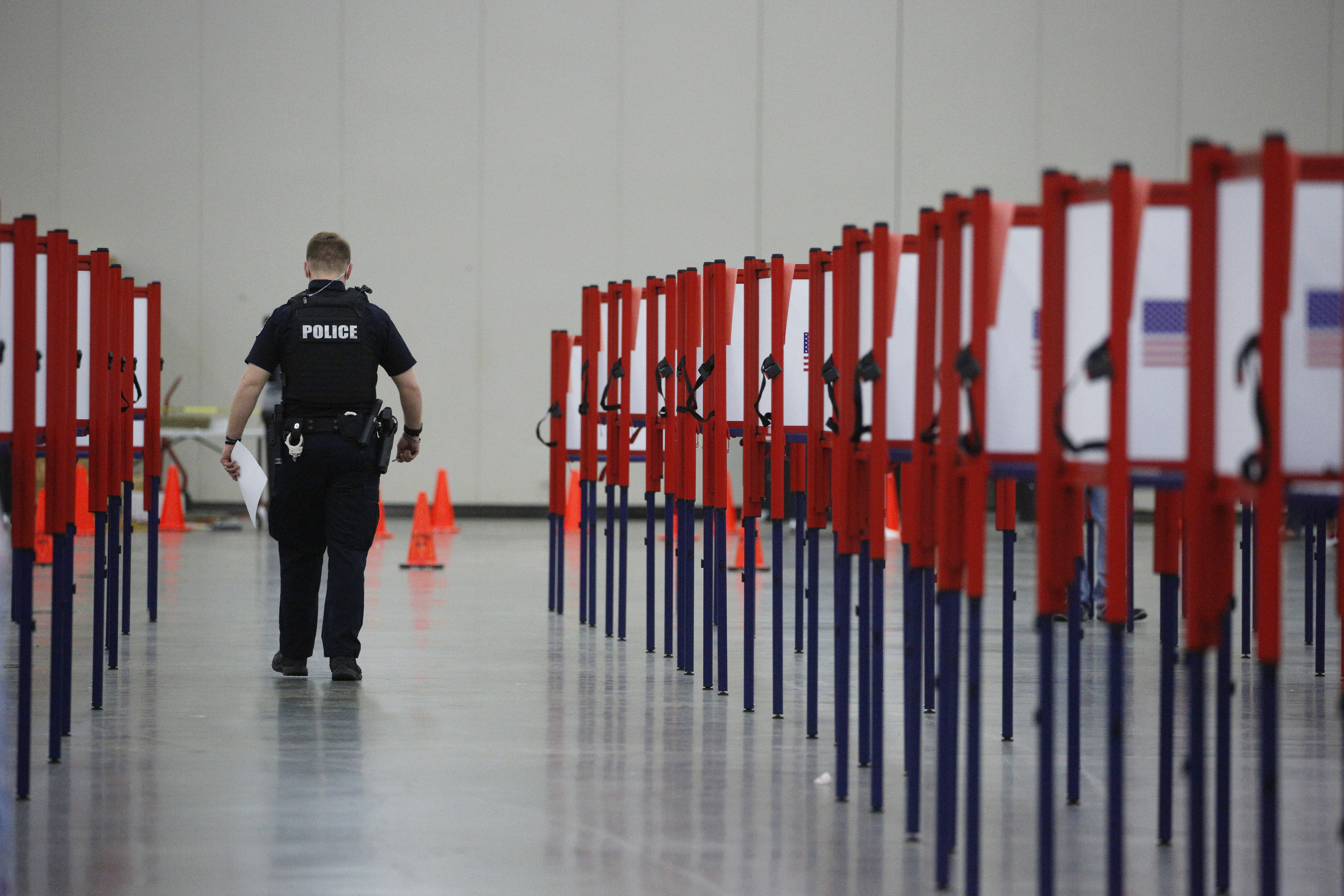 A Louisville Metro Police Department officer carries a ballot while voting at a polling location in Louisville, Kentucky, on June 23, 2020.