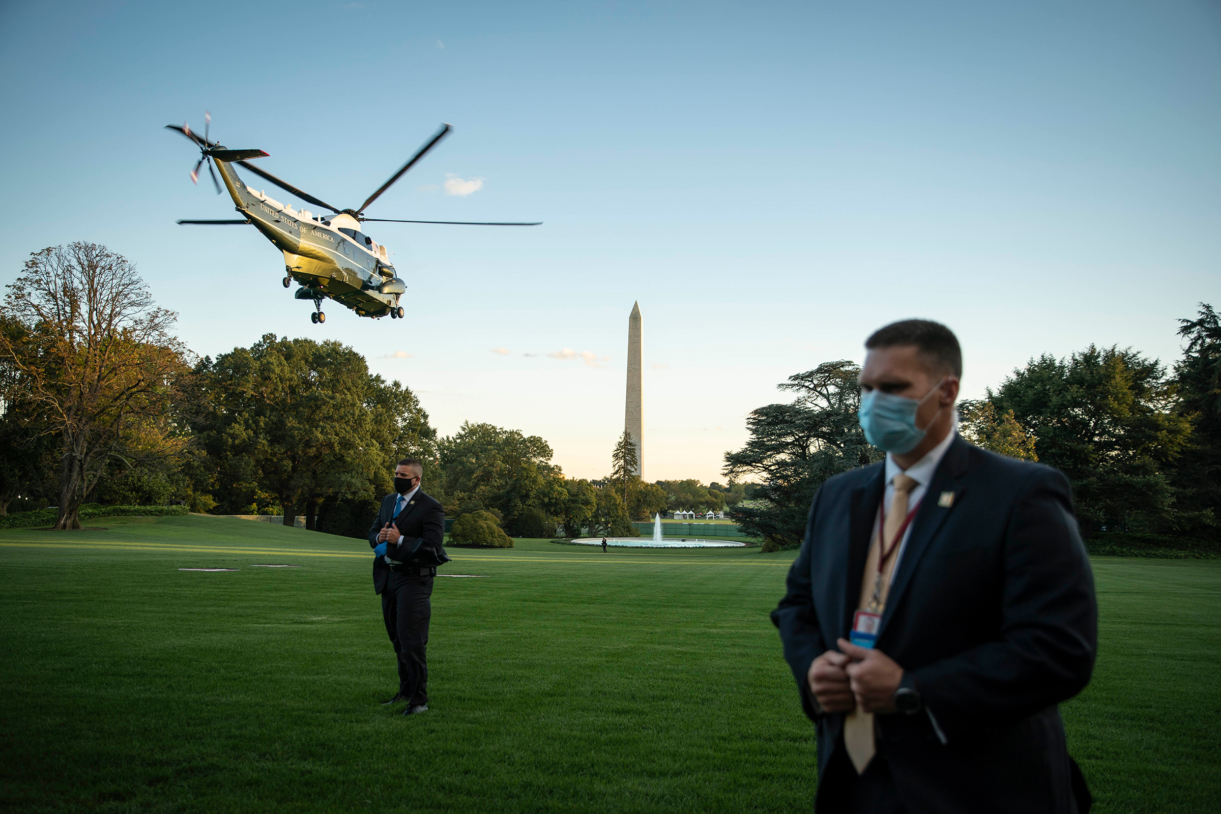 Secret Service agents wearing protective face masks stand by as Marine One, carrying President Trump, departs from the South Lawn of the White House on Oct. 2.