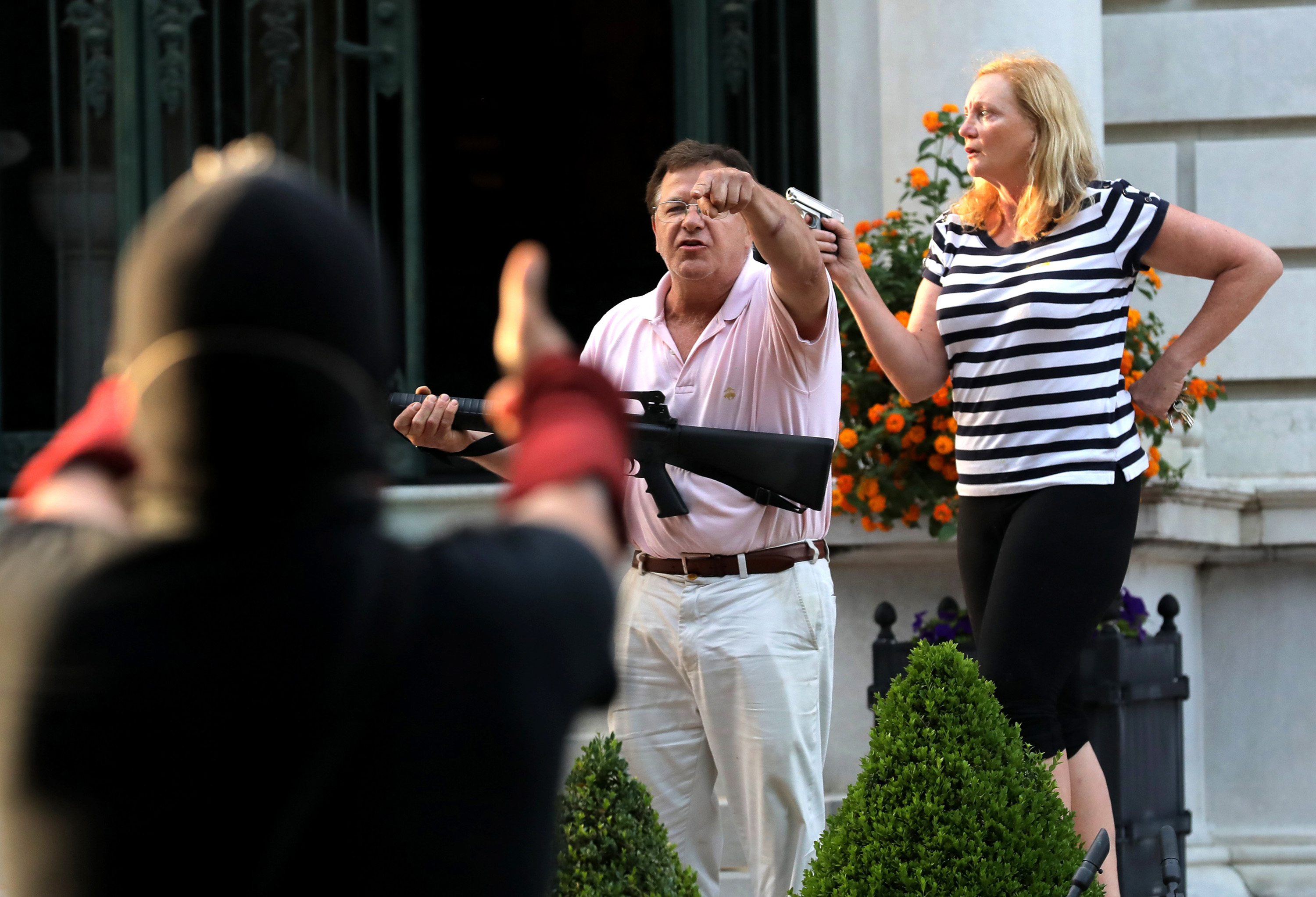 Armed homeowners Mark and Patricia McCloskey confront protesters marching to St. Louis Mayor Lyda Krewson's house on June 28, 2020 in St. Louis.