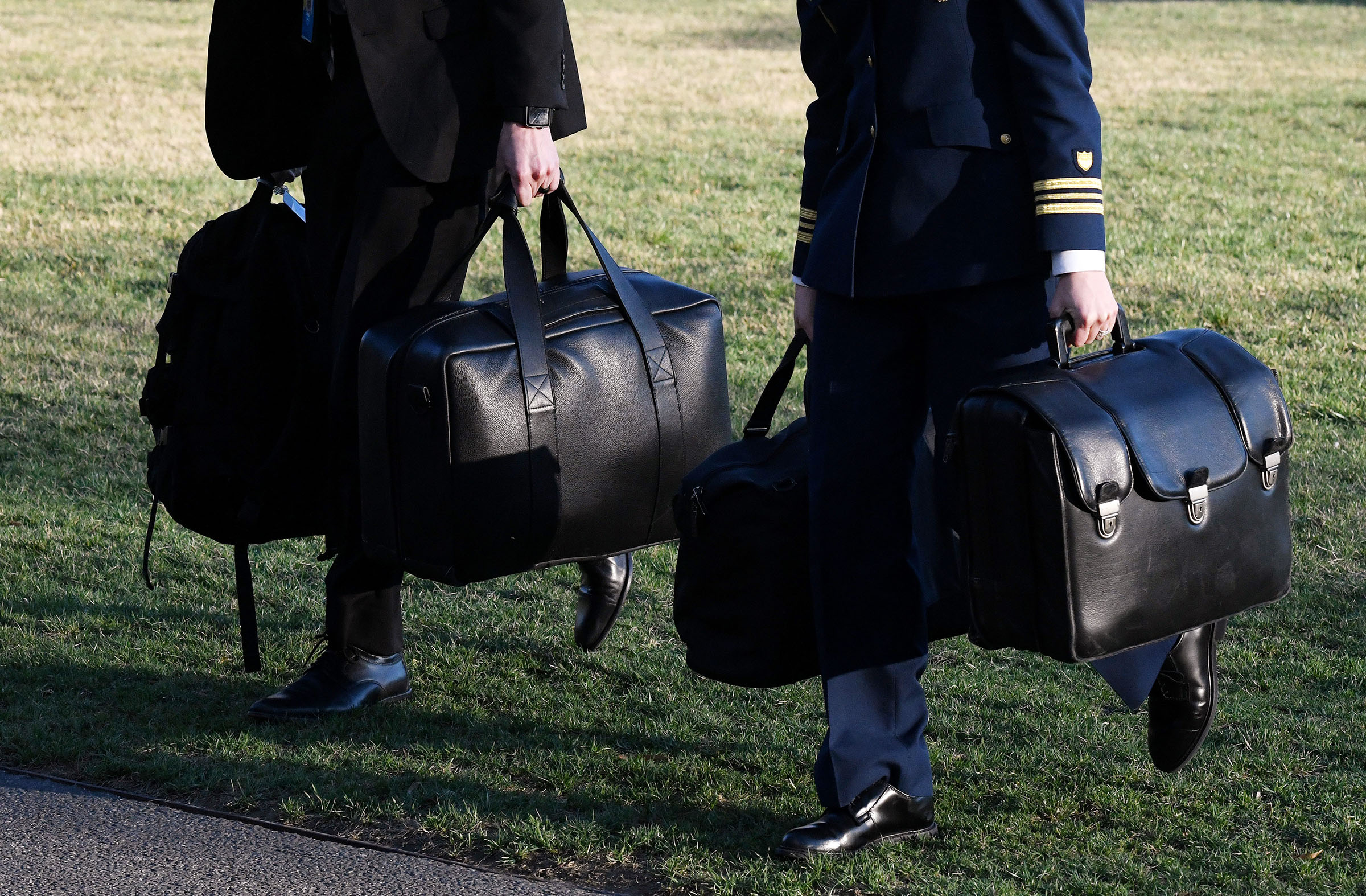 A military aide carries the nuclear football across the South Lawn at the White House in Washington, DC, on March 3, 2018.