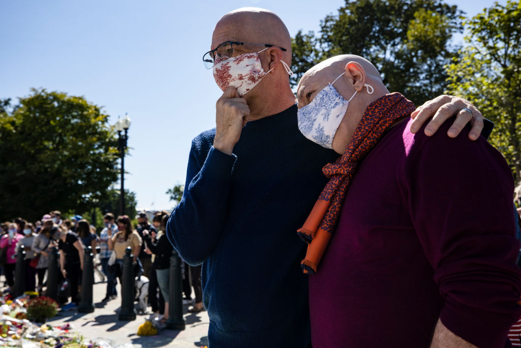 Michael Widomski, left, and David Hagedorn, right, embrace after leaving a photograph of Supreme Court Justice Ruth Bader Ginsburg joining them in marriage at the makeshift memorial for Justice Ginsburg in front of the U.S. Supreme Court on September 20, 2020 in Washington, DC. Justice Ginsburg officiated their wedding in 2013, two years before the Supreme Court cleared the way for gay marriages around the country in 2015. Justice Ginsburg has died at age 87 after a battle with pancreatic cancer.